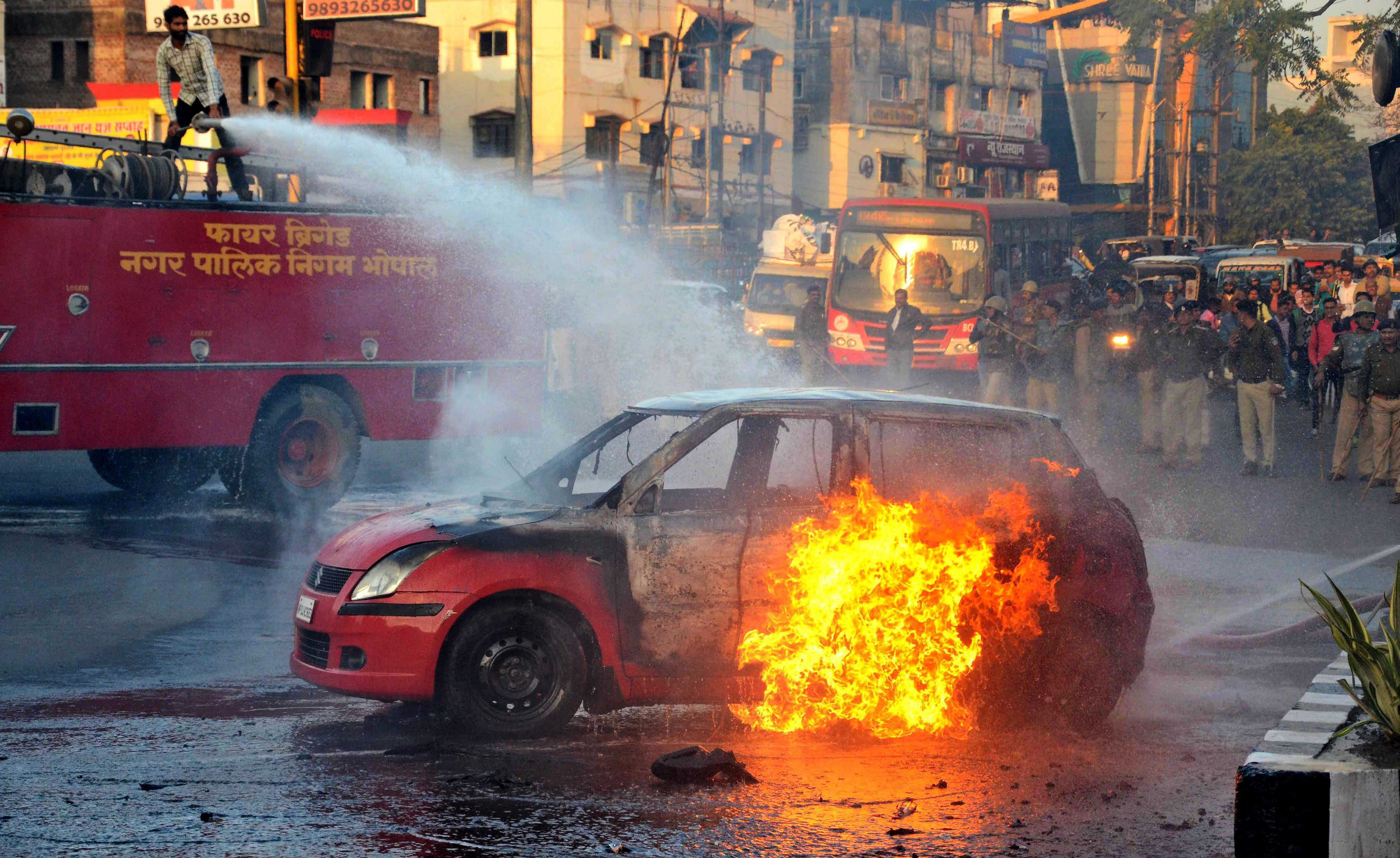 Firefighters in Bhopal try to douse the flames of a car Rajput groups set on fire protesting against Padmaavat. (Credit: PTI)