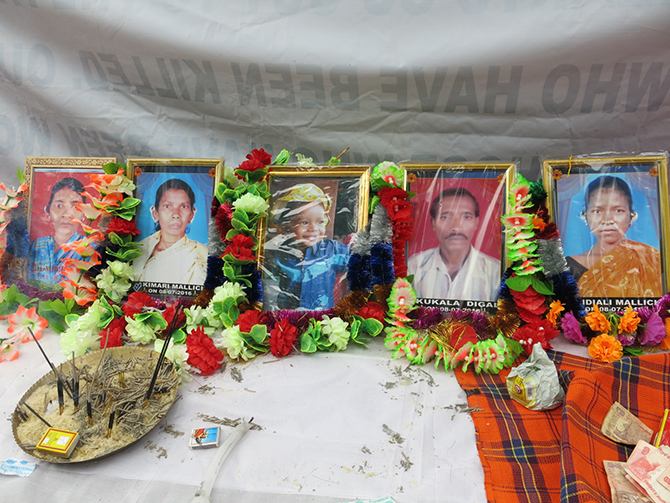 Photos of the five dead villagers on display at a memorial meeting in Gumudumaha village. Photo by Chitrangada Choudhury.