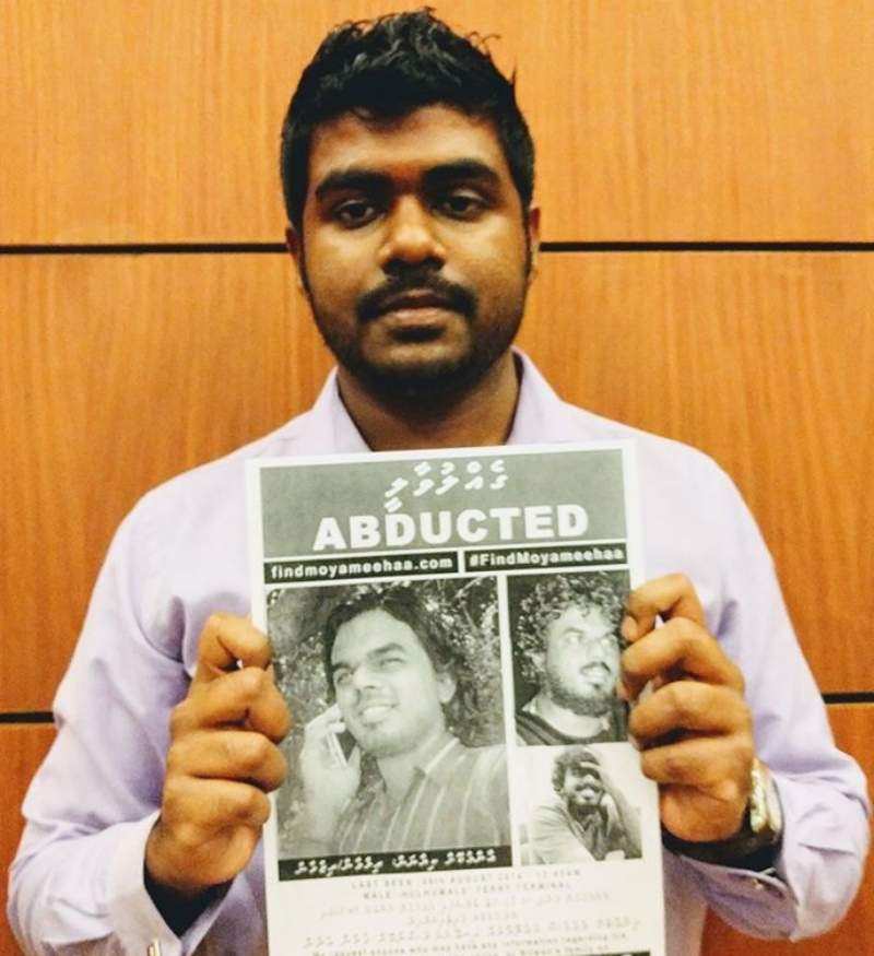 Rasheed with a poster of his friend, Ahmed Rilwan, who was abducted in 2014 . (Photo courtesy: Yameen Rasheed/Facebook).