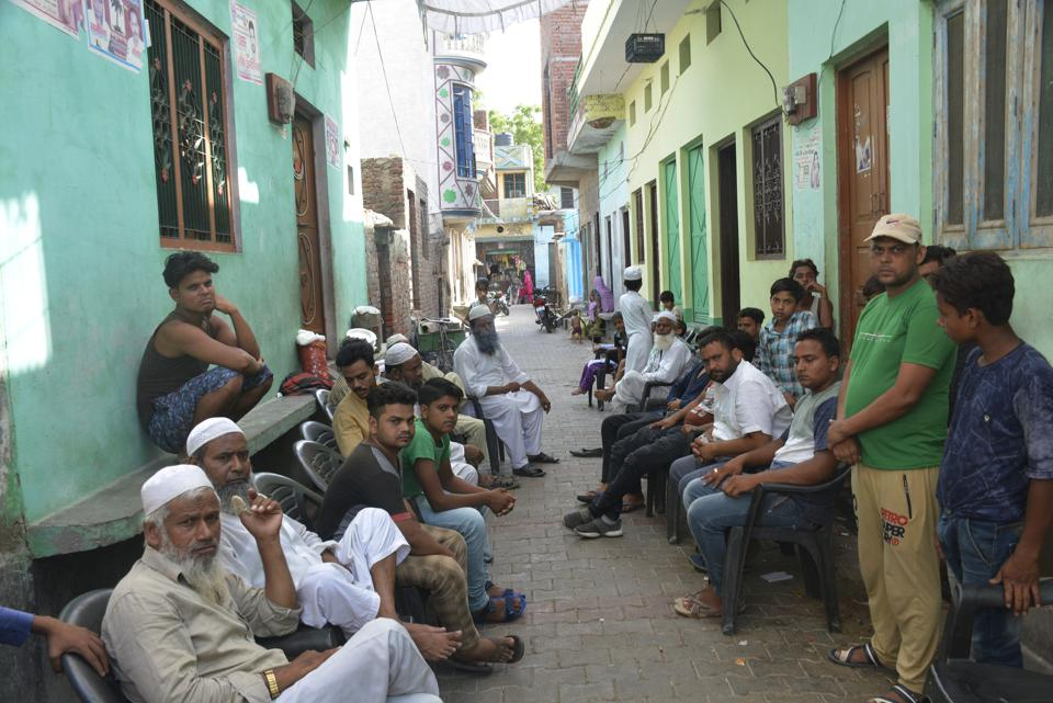 Relatives and neighbours at Qasim's house after he was lynched in Hapur. Photo credit: HT