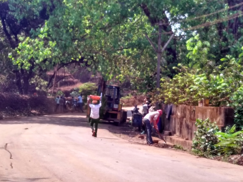 Employees of mining companies clear the debris near the road after villagers protested. (Photo credit: Pamela D'Mello).