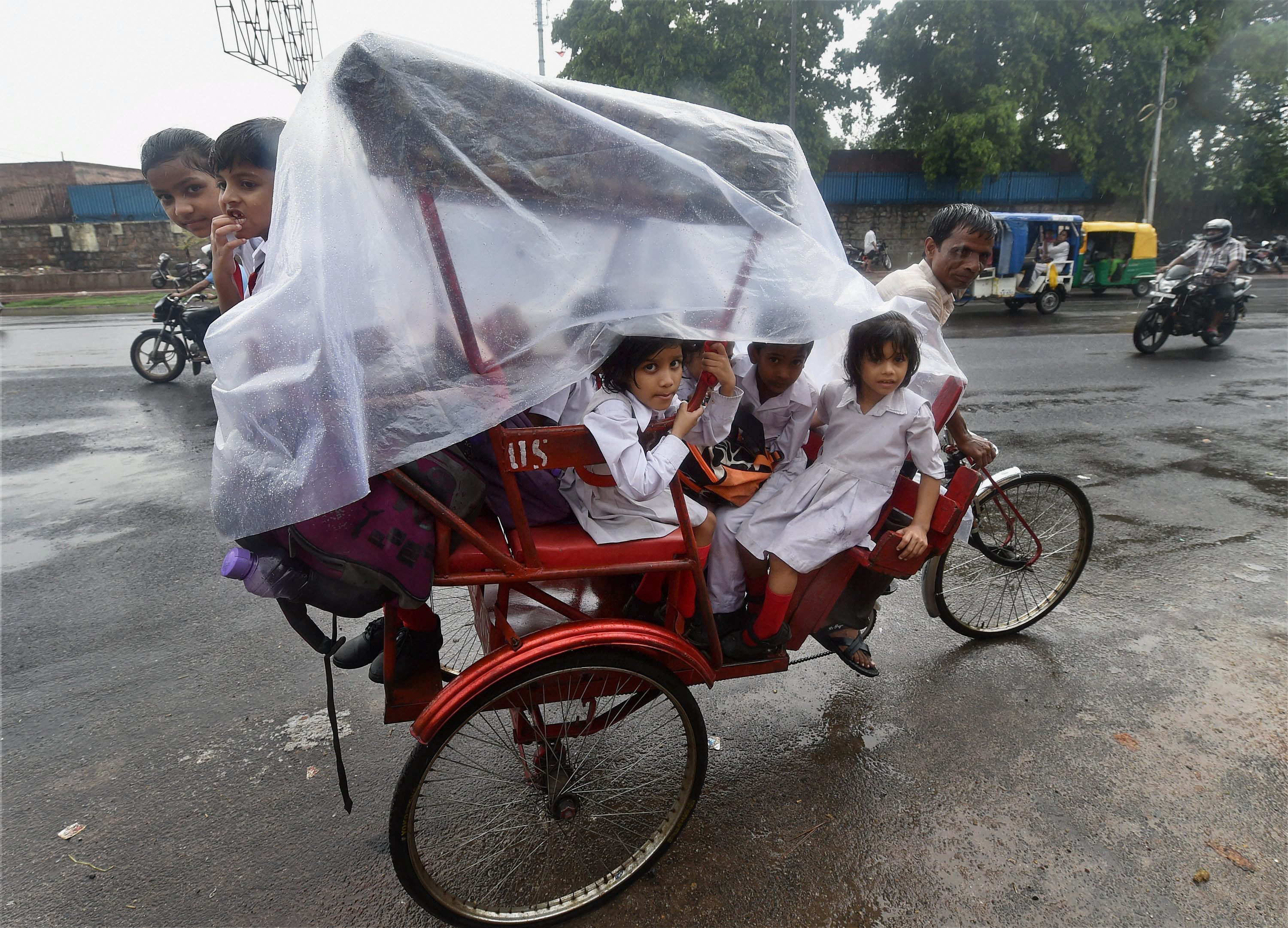 Schoolchildren take shelter in a cycle rickshaw as it rains in Delhi. (Credit: PTI)