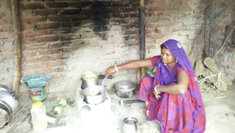 Sona Devi cooks on her wood stove. (Photo credit: Dhirendra K Jha).