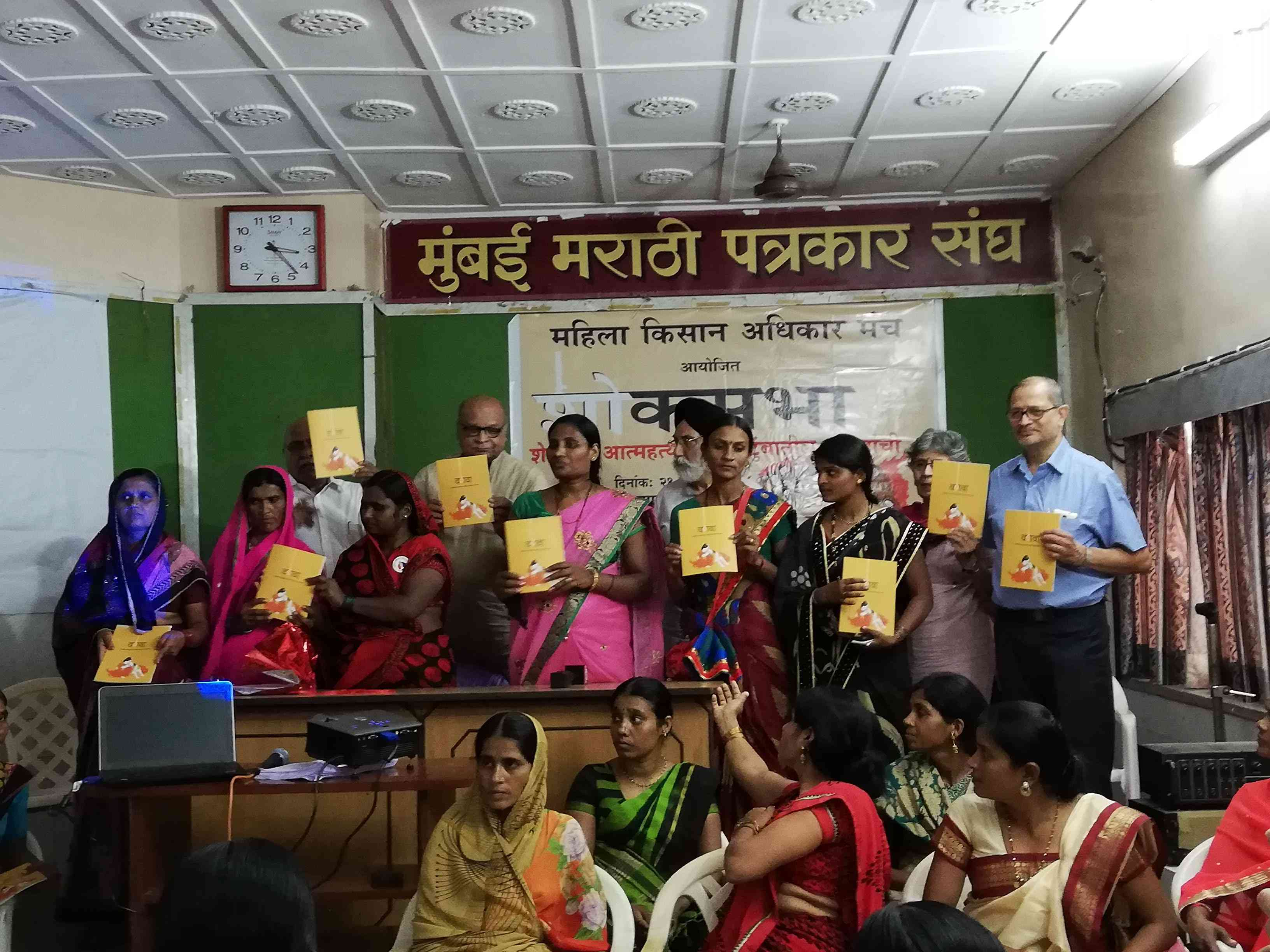Women hold up copies of their testimonies at the press conference. (Photo credit: Mridula Chari).