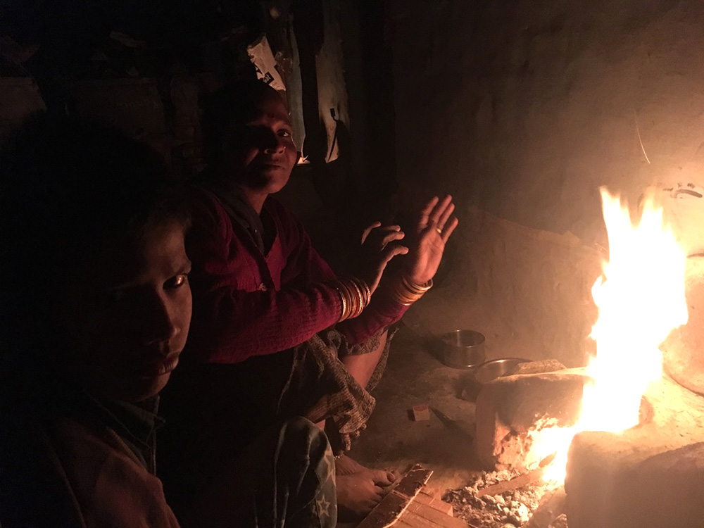 Andhera Gher slum residents keeping themselves warm by a wood-fueled fire on a cold November night. Photo credit: Menaka Rao.