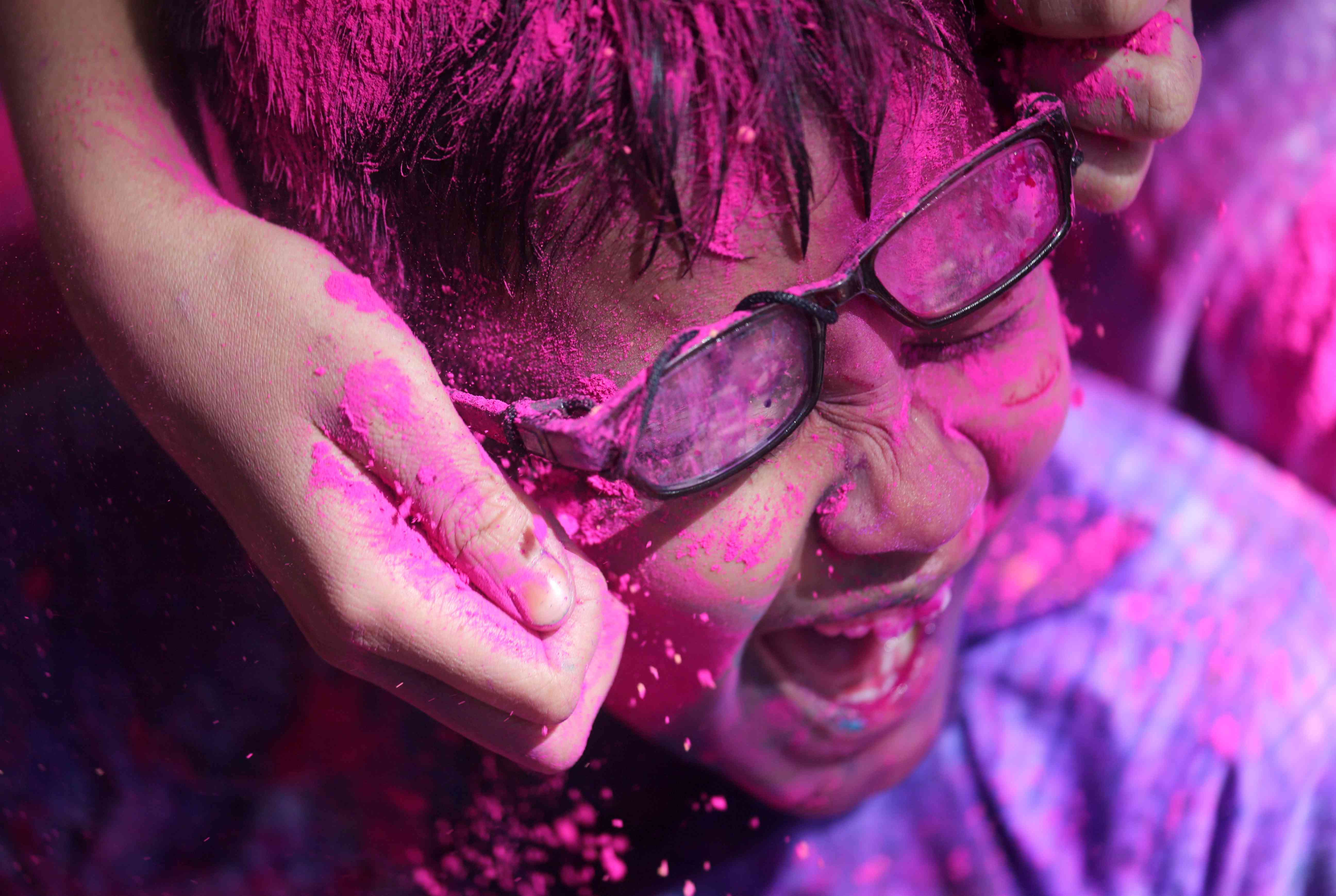 A child covered in colours during Holi celebrations in Mumbai. | Credit: Reuters
