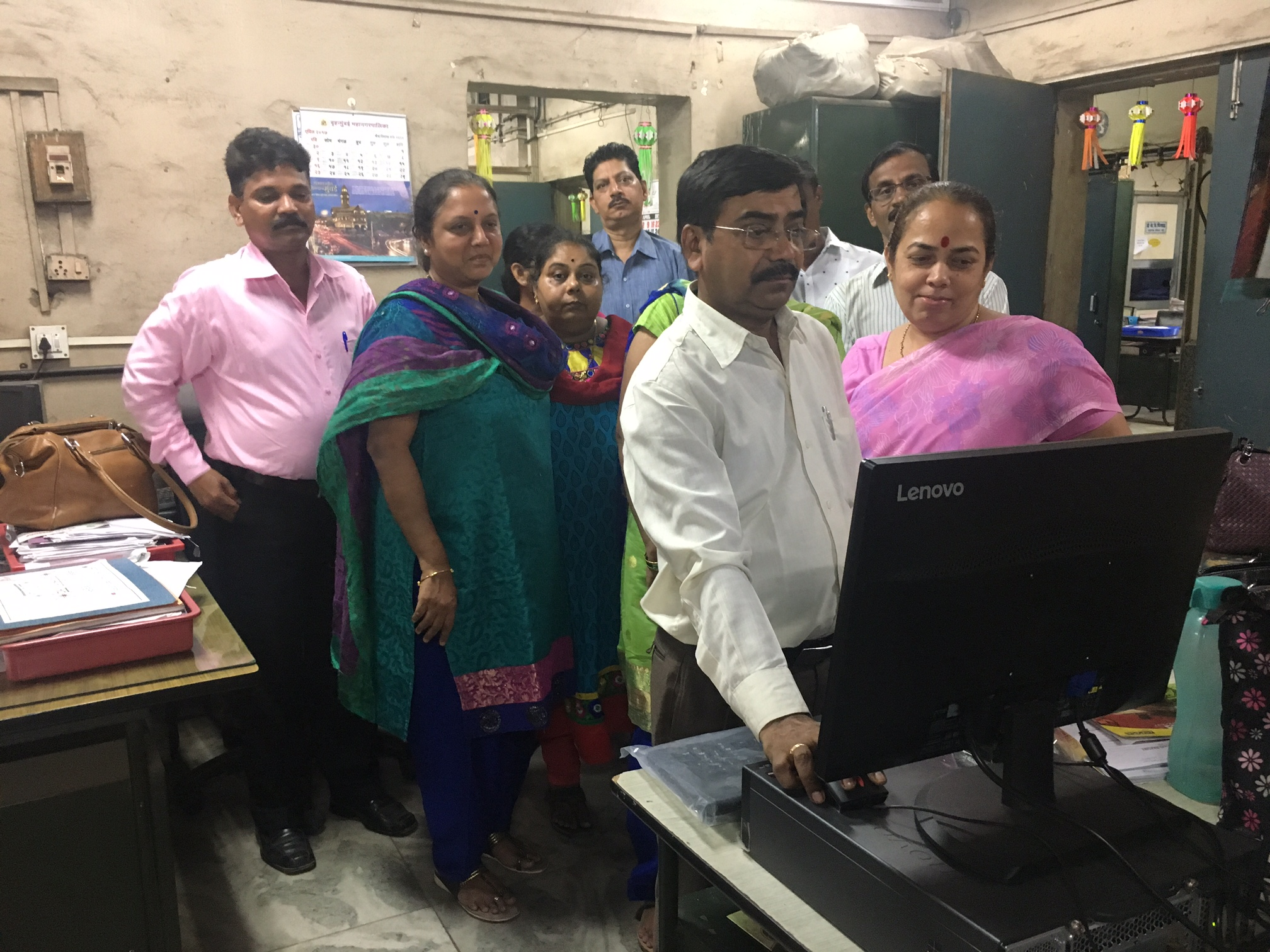 Employees of the R-North ward office line up at the Aadhaar-enabled biometric attendance system. (Credit: Priyanka Vora)