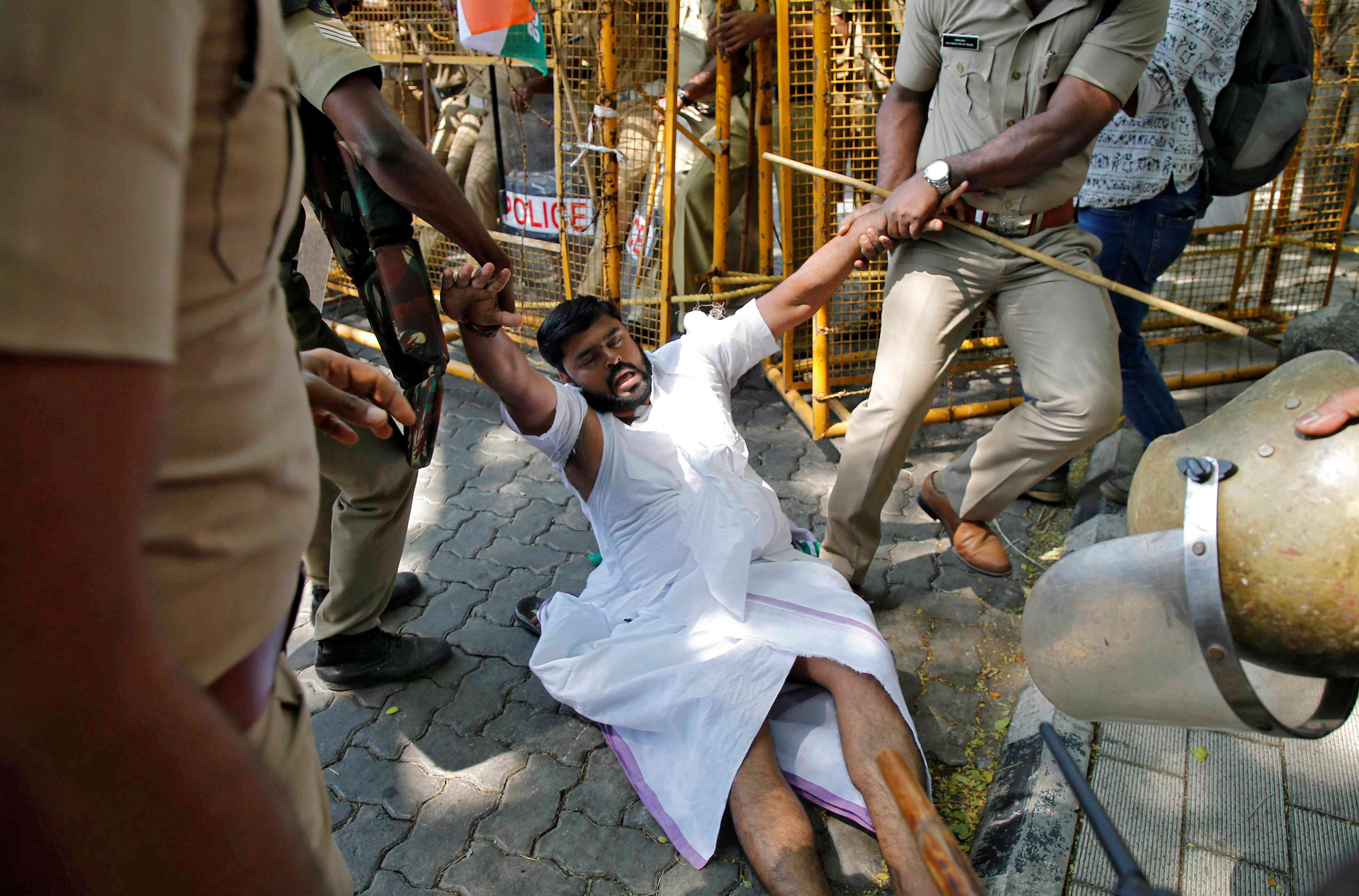 Police detain a protestor during a demonstration in Kochi against the entry of two women into the Sabarimala temple. (Photo credit: Sivaram V/Reuters).