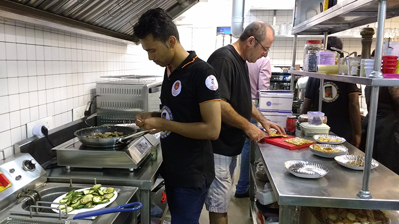 Anil Kurup and Carlos Perez at work in the café's kitchen.