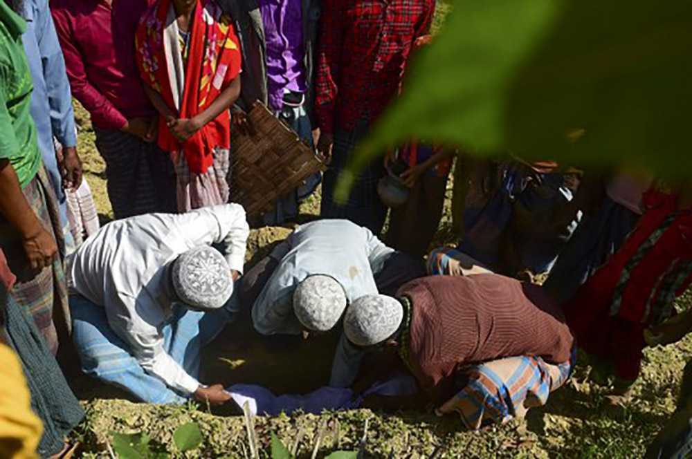 Myanmar Rohingya refugees bury the body of six-month-old Alam in a refugee camp in Teknaf, in Cox's Bazar district, on November 26, 2016. Image Credits: AFP