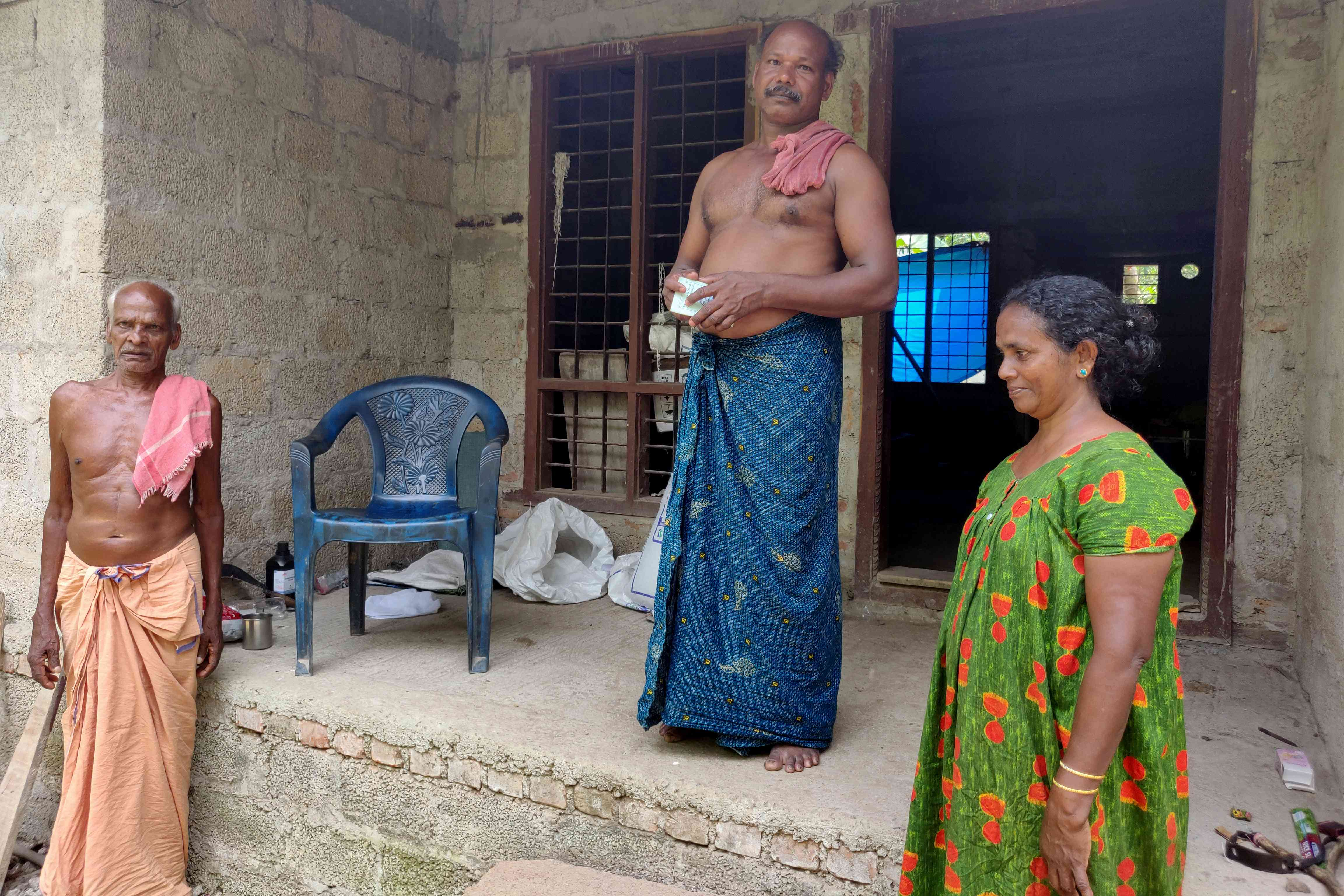 Babu Kuttan, centre, with his wife and father at their home in Champakkulam. Photo credit: TA Ameerudheen