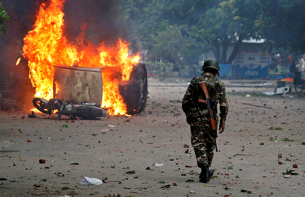 A security personnel walks towards a burning vehicle in Panchkula, Haryana, where the government claimed full arrangements were made to control the violence. (Credit: Cathal McNaughton/Reuters)