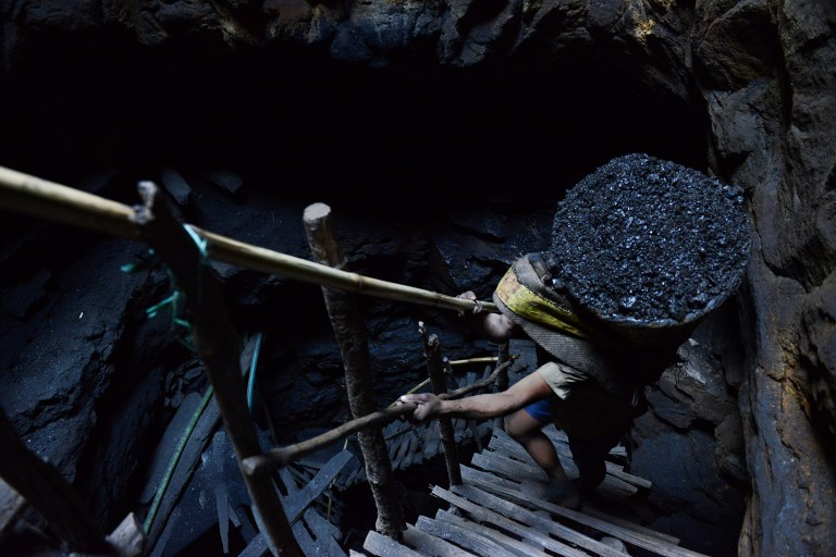 In this photograph taken on January 31, 2013, a miner slowly carries a heavy load of wet coal on a basket hundreds of feet up on wooden slats that brace the sides of a deep coal mine shaft near Rimbay village in Meghalaya. Photo credit: AFP/ Roberto Schmidt