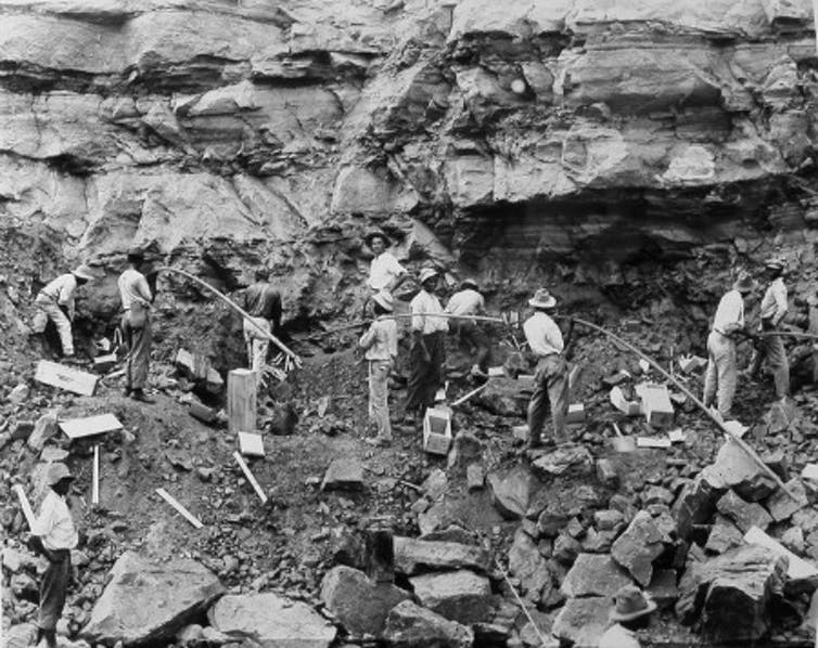 Loading shot holes with dynamite to blast a slide of rock in the west bank of the Culebra Cut, February 1912. Photo Credit: National Archives at St. Louis/local Identifier 185-G-154