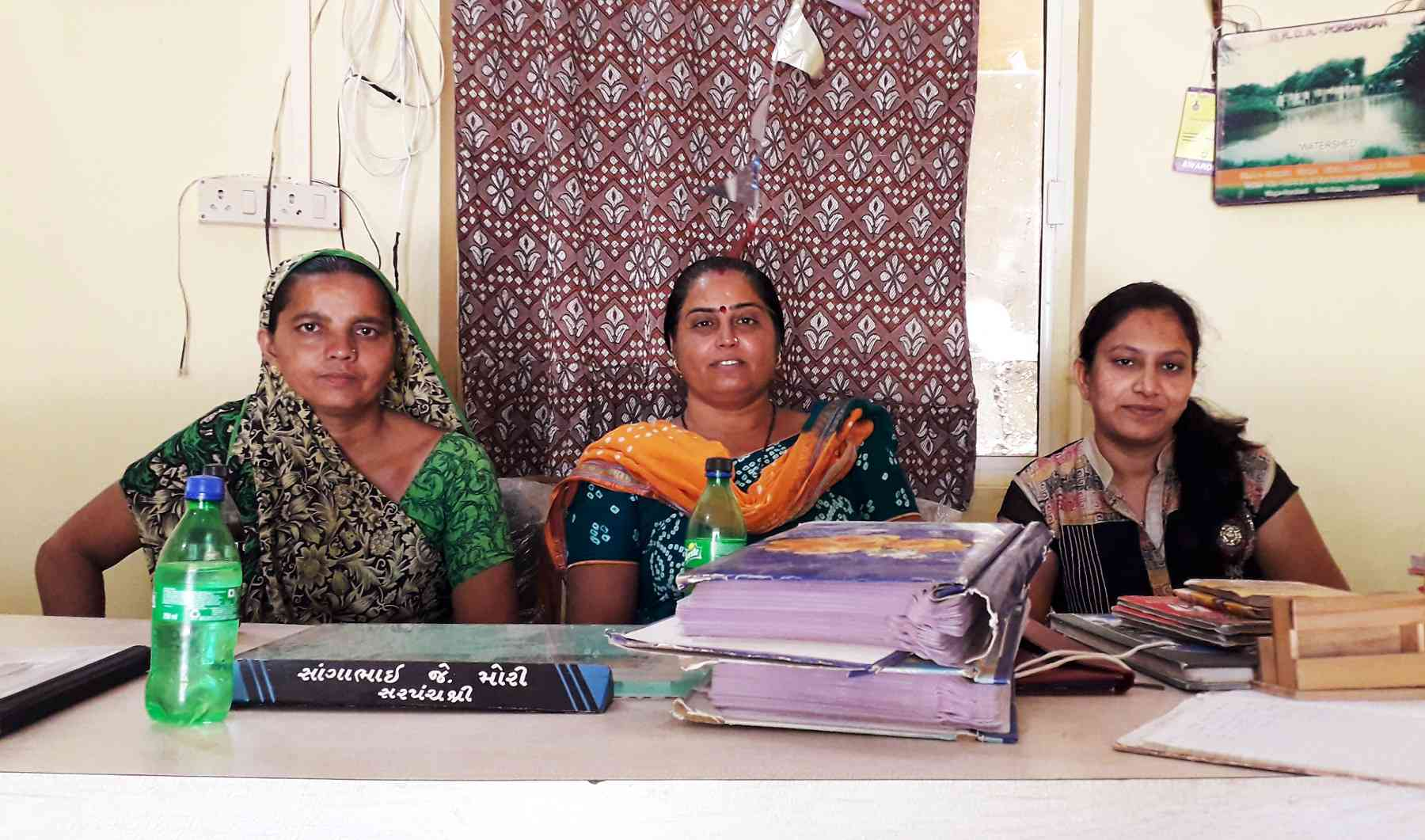 Rana Bordi's women panchayat members (left to right): Amina Isub, Laxmiben Mori and Bhavna Vara. The nameplate on the sarpanch's desk has Laxmiben's husband's name on it. Photo: Aarefa Johari