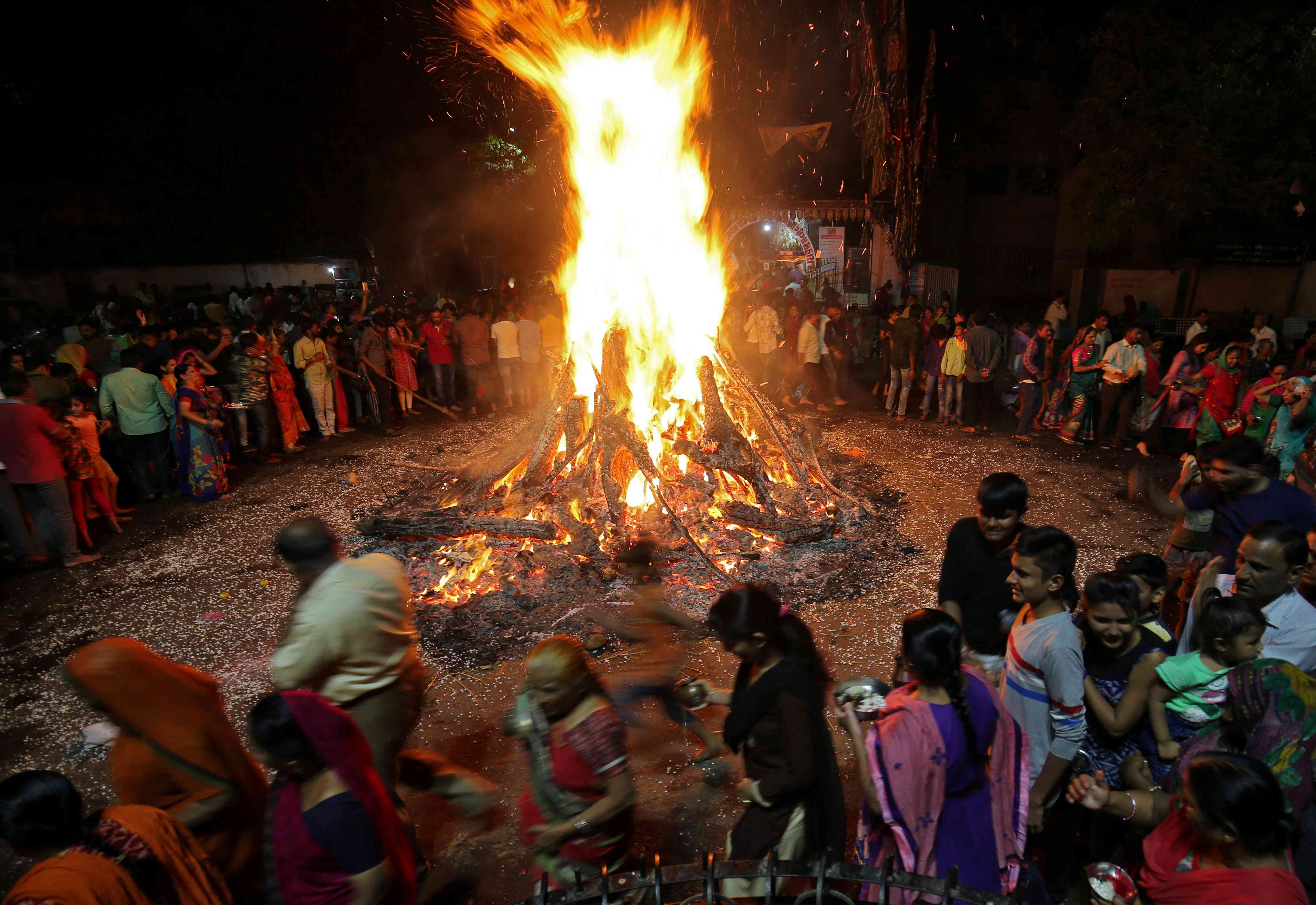 Devotees walk around a bonfire during a ritual called Holika Dahan in Ahmedabad on Wednesday night. | Credit: Reuters