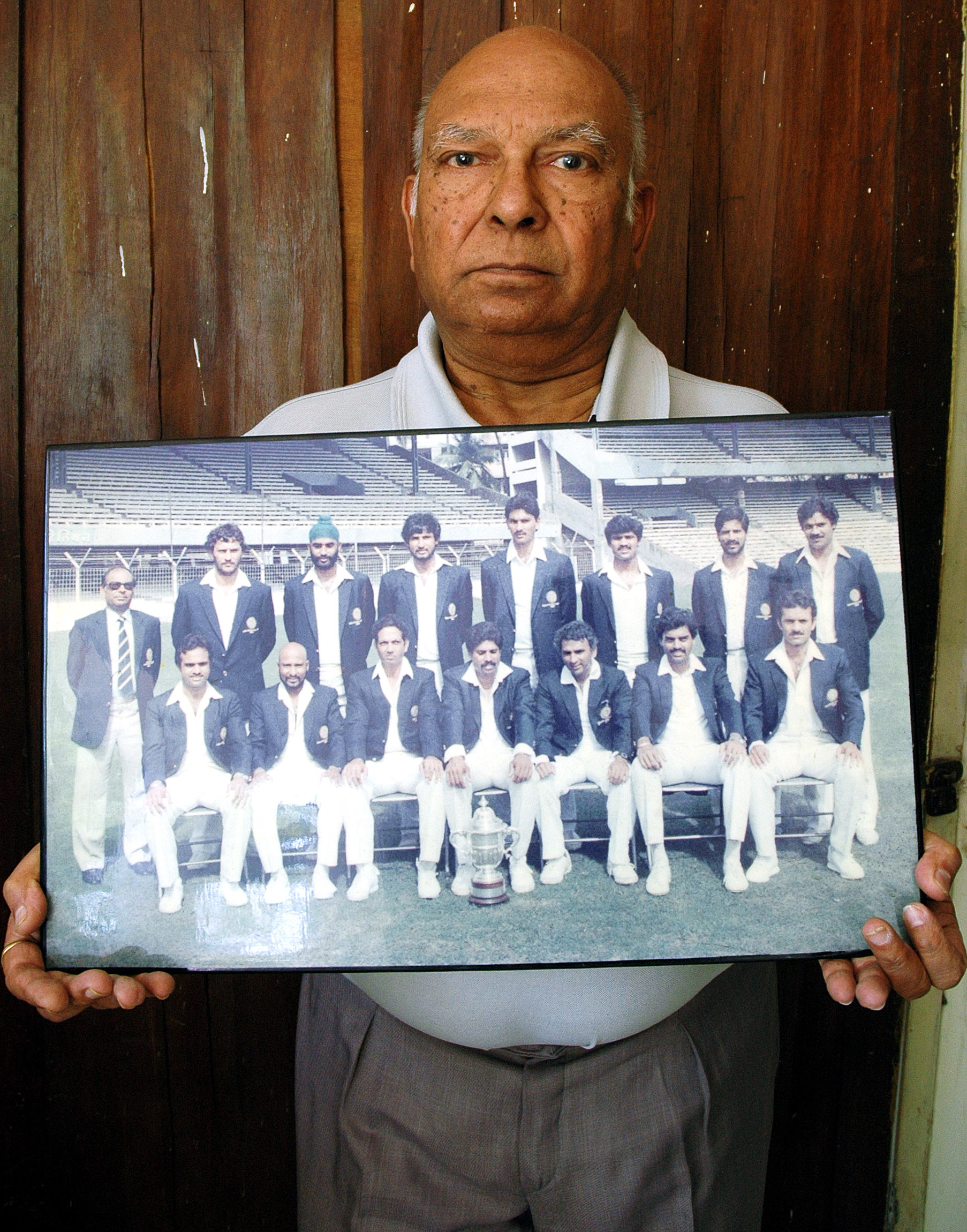 Manager of the team Man Singh holding the group photo that was shot in Mumbai / AFP