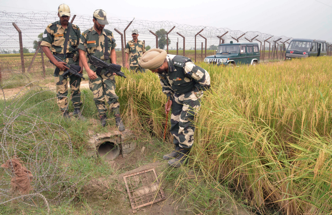 BSF officers inspect a site near the India-Pakistan border in Punjab where packets of confiscated heroin were found. The force deals with high-stakes drug smuggling and militant threats daily. (Credit: Narinder Nanu / AFP)