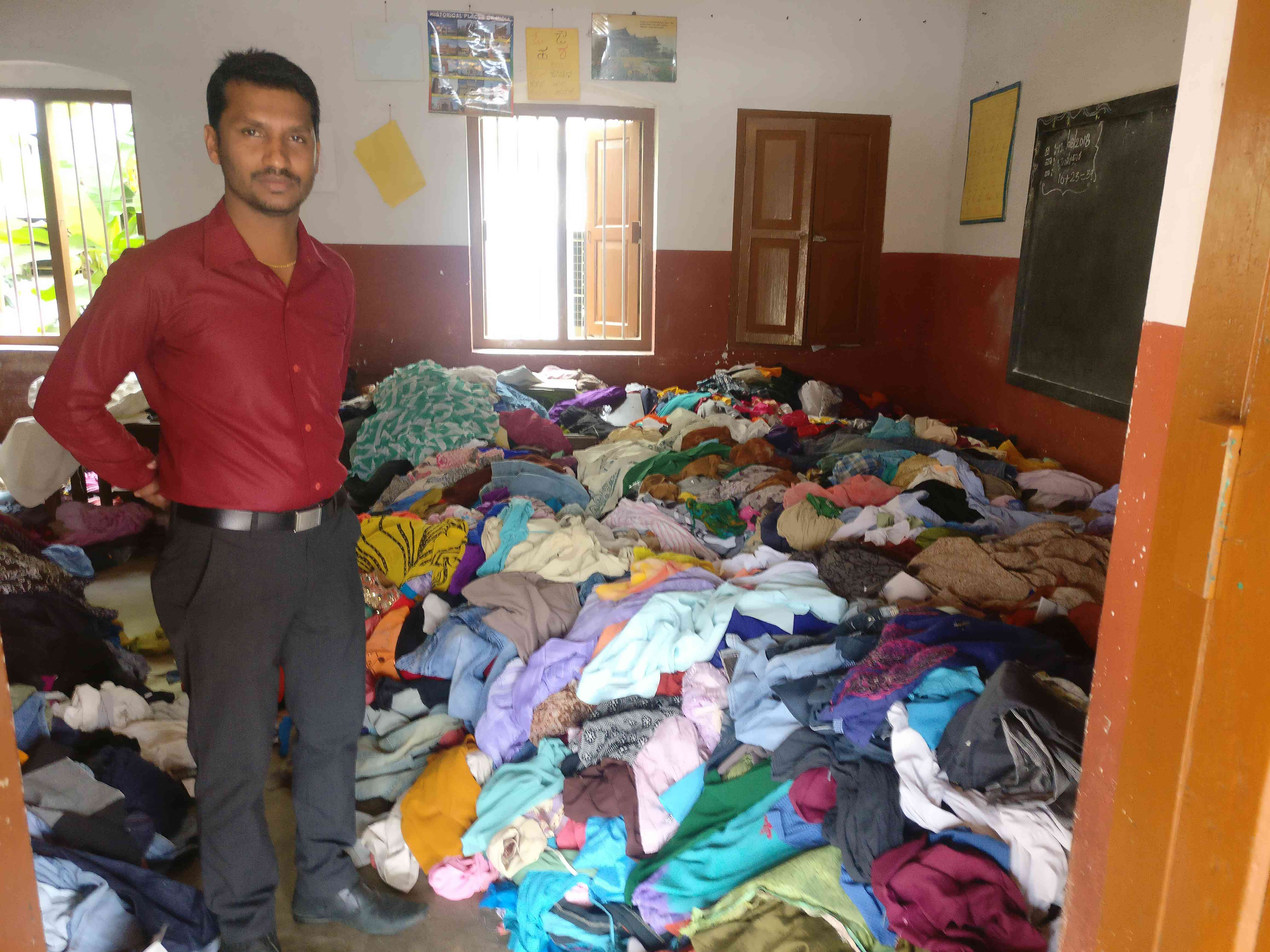 Harish stands in a room full of unusable clothes donated to flood victims in Kodagu. (Credit: Nayantara Narayanan)