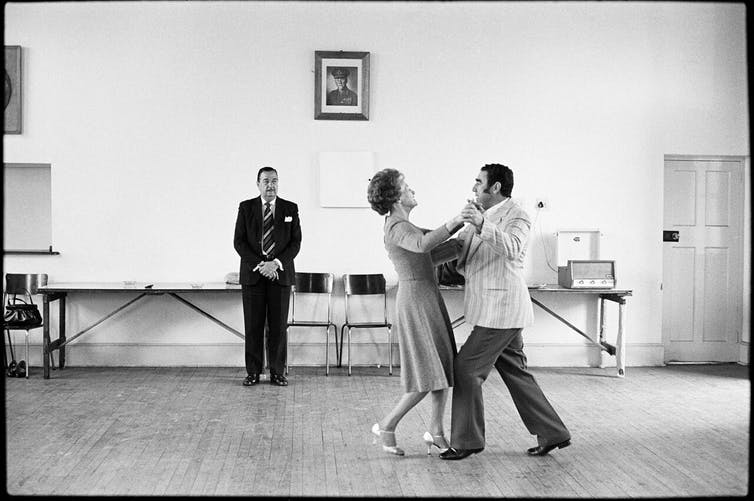 Dancing-master Ted van Rensburg watches two of his ballroom pupils, swinging to a record of Victor Sylvester and his Orchestra, the MOTHS' Hall at the old Court House, Boksburg. 1980. David Goldblatt