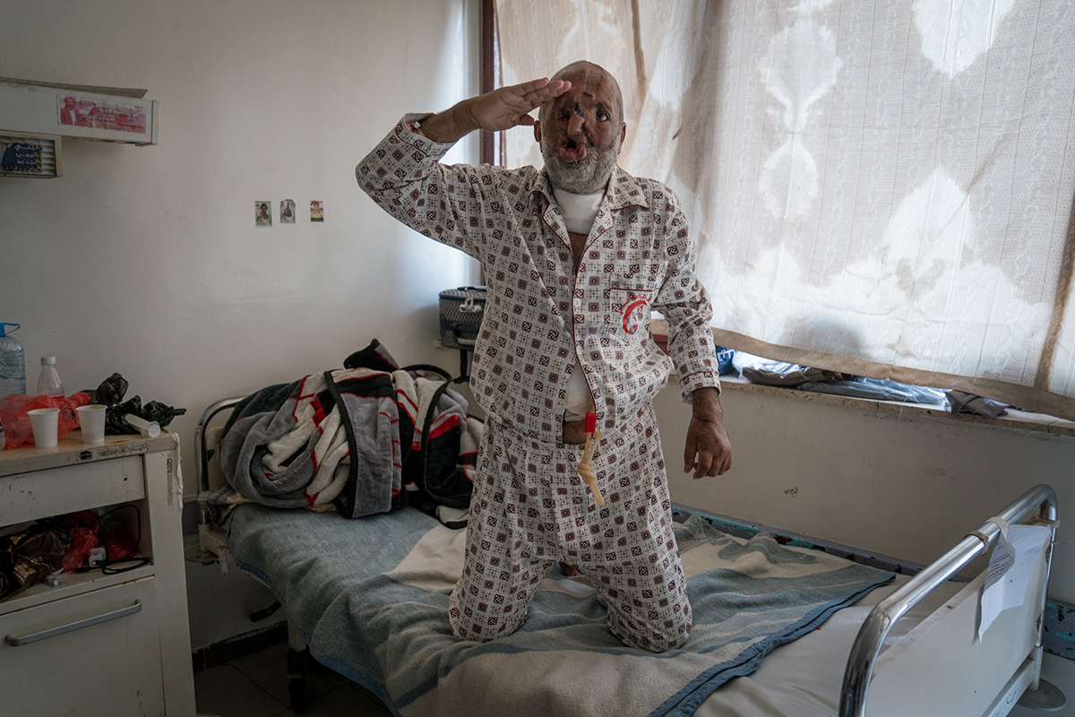 Photograph by Giles Clarke, from the series 'Yemen: Victims of War'. An injured pro-Houthi soldier salutes while being photographed on his hospital bed at the The Al Thawra Hospital, Sana'a, Yemen. Yemen has been crippled by a war between forces loyal to the internationally-recognised government of President Abdrabbuh Mansour Hadi and those allied to the Houthi rebel movement. © Giles Clarke, United Kingdom, Shortlist, Professional, Current Affairs & News (Professional competition), 2018 Sony World Photography Awards.