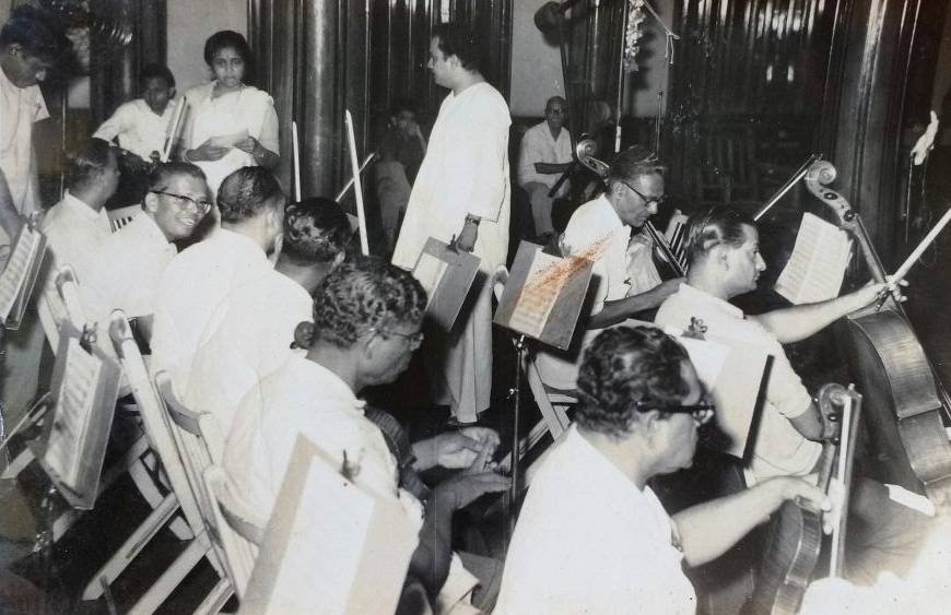 The music director with Asha Bhosle and the violinists.