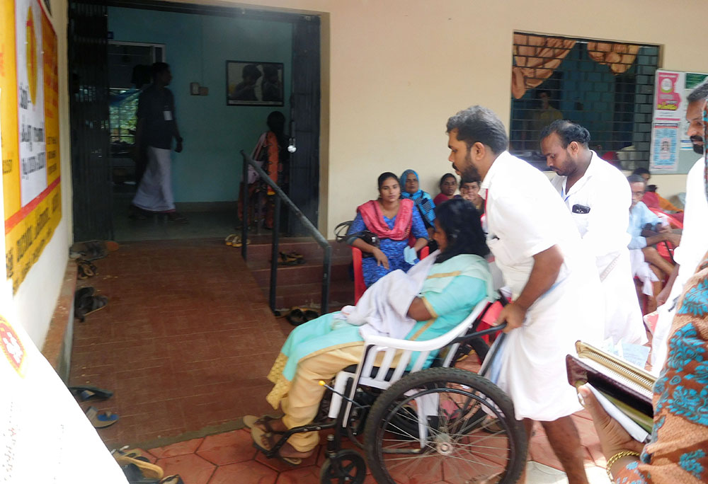 Volunteers carry patients on wheelchair at the Community Health Centre in Koorachundu. Photo TA Ameerudheen