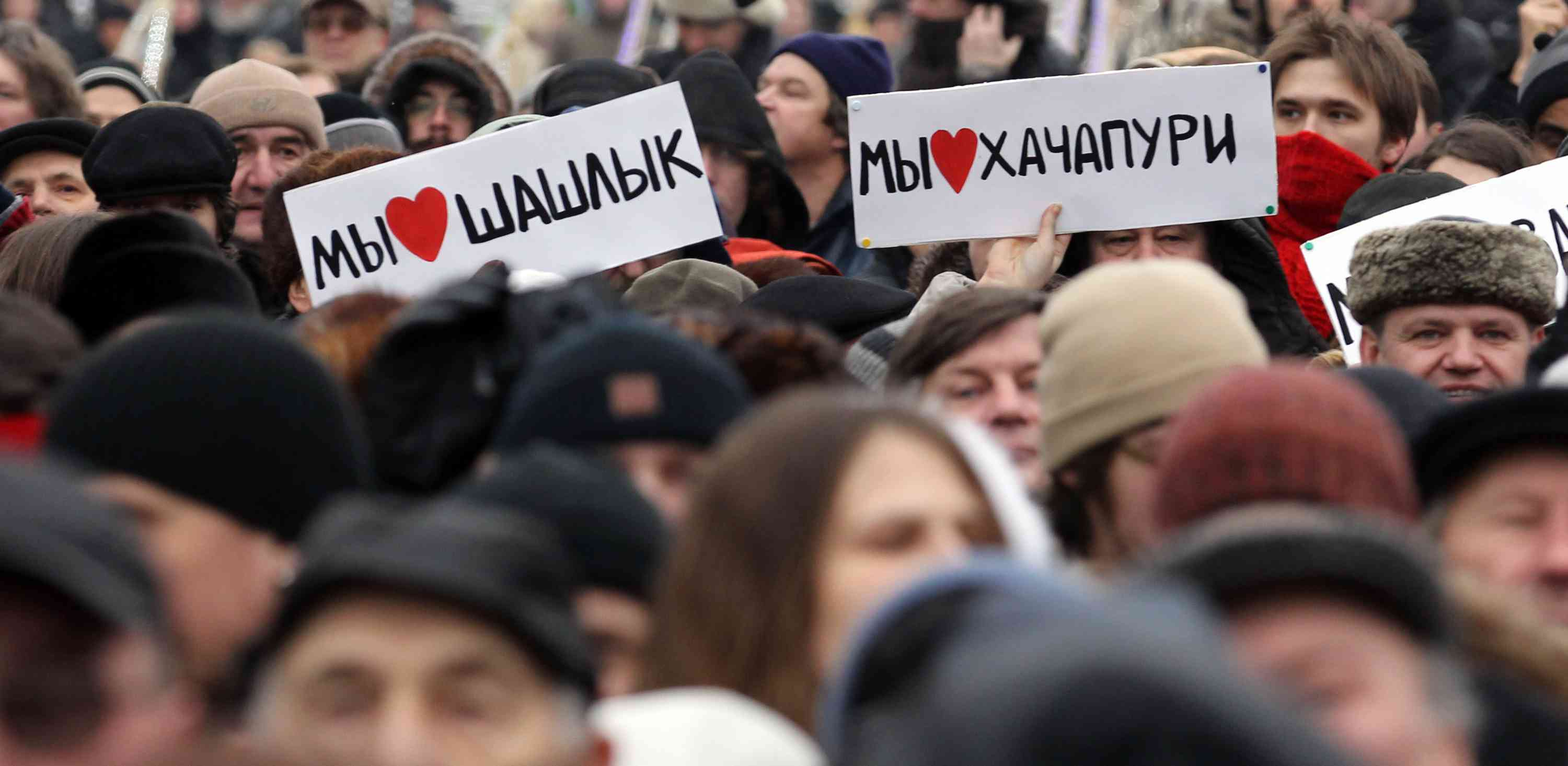 "People hold posters reading ""We like kebab!"" and ""We like khachapuri!"" (Georgian cheese pastry) during a rally ""Russia without Fascism"", against the xenophobic state of public opinion in a society in Moscow, on December 26, 2010. Photo credit: Alexey Sazonov/AFP"