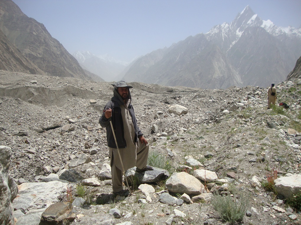 Member of monitoring team standing in front of a Debris-covered Glacier. Courtesy:  Water and Power Development Authority