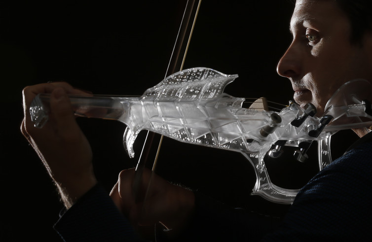 French engineer and professional violinist Laurent Bernadac plays a 3D printed violin made of transparent resin. Image Credits: Christian Hartmann/Reuters