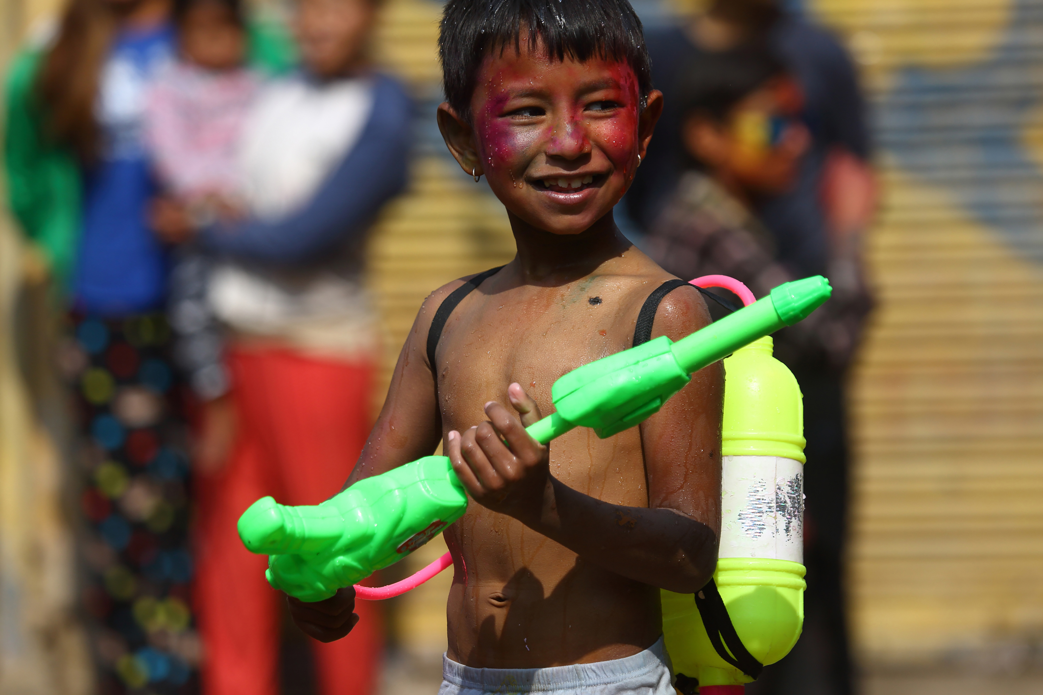 A boy plays with his watergun as he celebrates Holi in Lalitpur, Nepal, on Thursday. (Image credit: Gopen Rai/AFP)