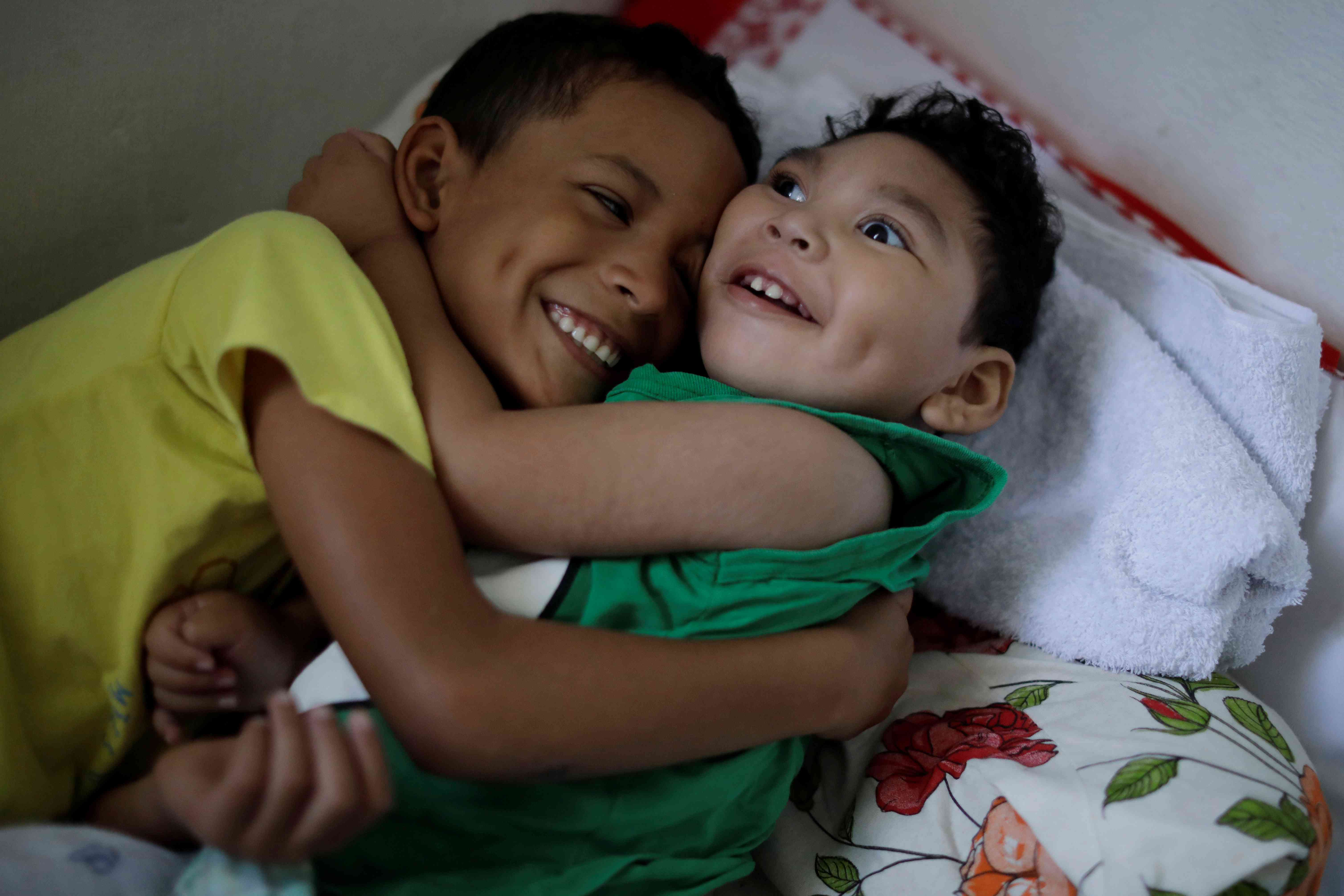 """Daniel Vieira, who is two years old, and was born with microcephaly, is greeted by his brother at their house in Olinda, Brazil, August 7, 2018. During her pregnancy, Daniel's mother Jackeline Vieira de Souza learned that her son had microcephaly. """"When he was born, I fell in love with him because I knew he would be a good thing in my life, even with the difficulties I would have to face."""" Daniel's father separated from Jackeline shortly after learning that his son had microcephaly. He pays a small amount of family support every month, in addition to a monthly check that Jackeline gets from the government. It takes several hours to travel by bus between their home in Olinda and Recife, where Daniel goes for treatments. Lately, those trips are somewhat less frequent, and Jackeline believes Daniel's health is more stable. She has no illusions that her son will ever walk, eat on his own or live a normal life. Yet in many ways she is grateful for her """"miracle"""" baby, who she says makes her feel """"happy and more accomplished"""". (Photo: Ueslei Marcelino/Reuters)"""