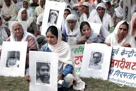 Sikh widows, holding portraits of Congress leaders and police officers allegedly involved in the 1984 violence, at a demonstration in Delhi in 2002. (Credit Raveendran / AFP)