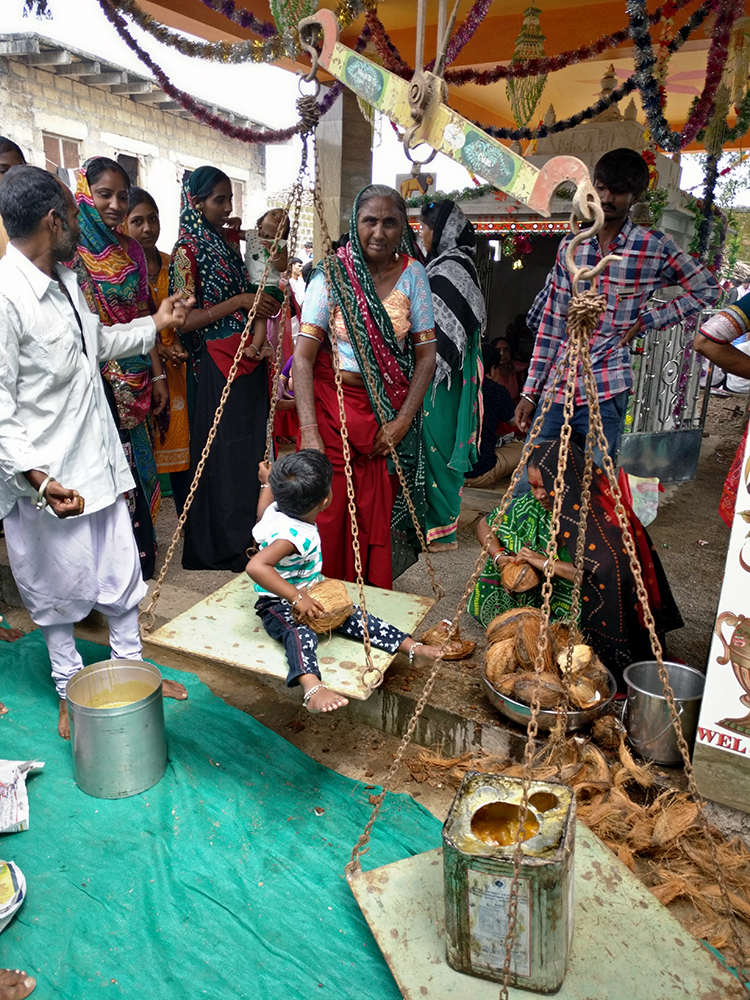 Children being weighed on a weighing scale. Parents pledge to donate jaggery equivalent to their child's weight asking for the Goddess to bless the kid with good health, education, success. Photo credit: Riddhi Doshi