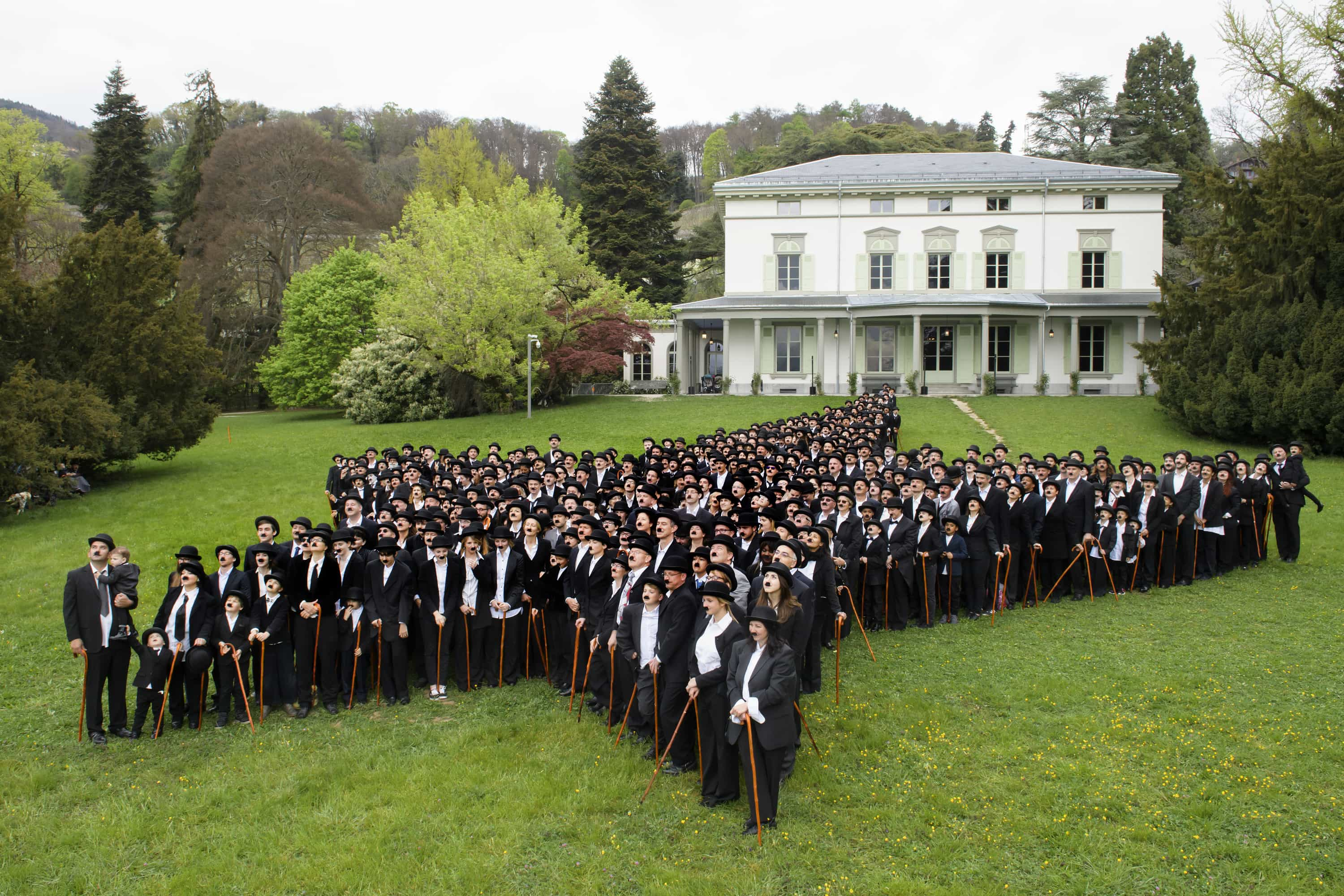 Fans dressed as Charlie Chaplin form a giant star in front of the Manoir de Ban. [Credit: Richard Juilliart/AFP]