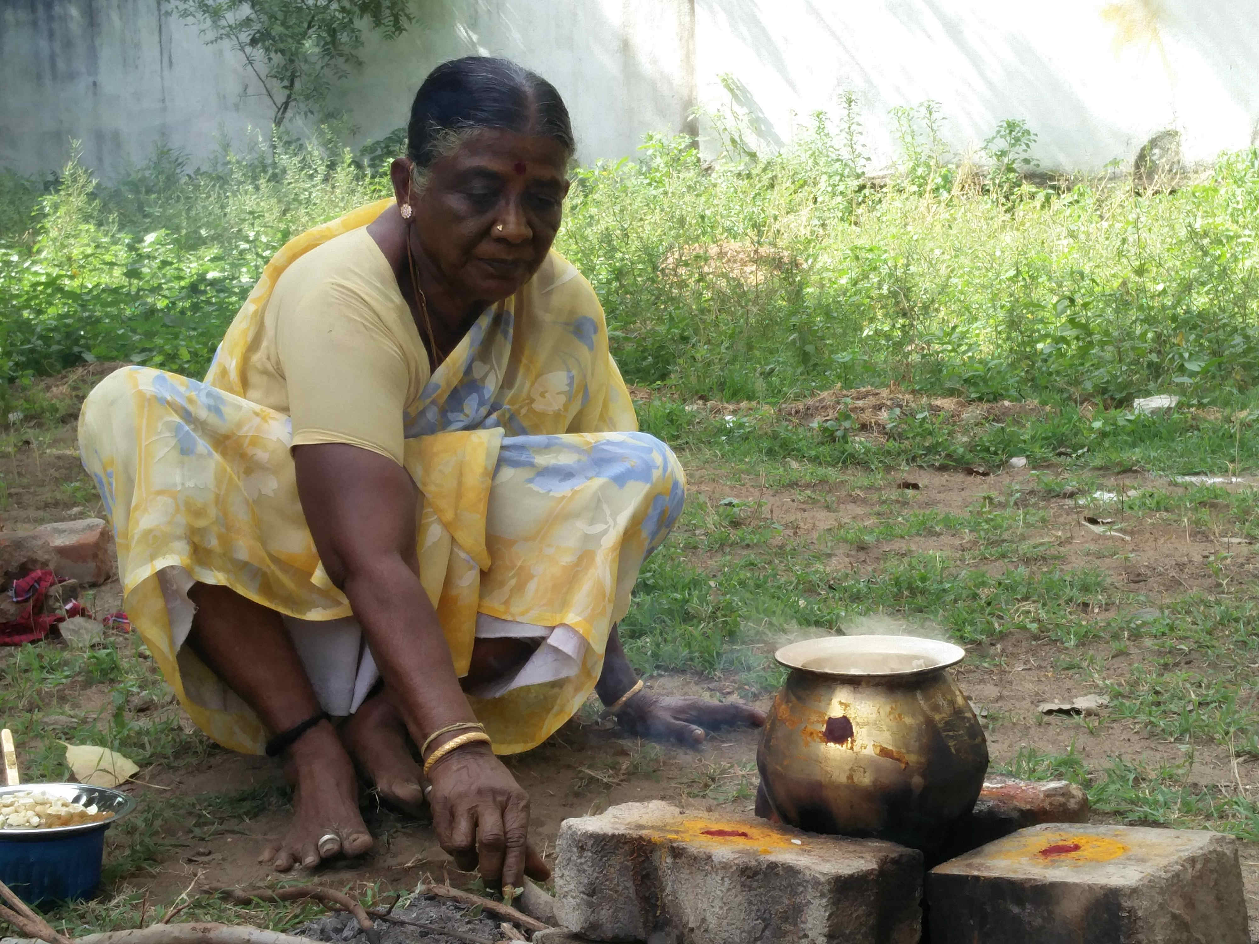 A lady preparing Pongal, a popular rice dish.