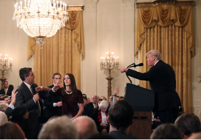 A White House staff member reaches for CNN reporter Jim Acosta's microphone as he questions President Donald Trump. (Credit: Jonathan Ernst / Reuters)