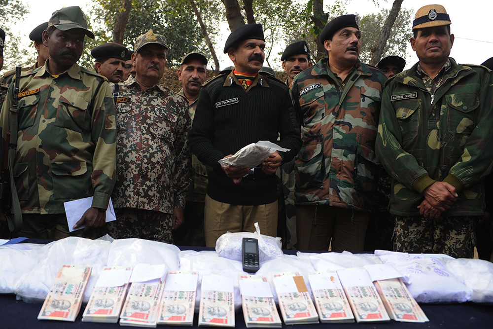 Indian Border Security Force Inspector General  Aditya Mishra and Deputy Inspector General Sanjeev Bhanot pose with 17 packets of confiscated heroin, and fake Indian Rupees during a press conference, held near the India-Pakistan Border at Bharopal, on January 18, 2012. Credit: Narinder Nanu/AFP