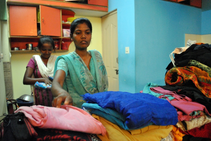 Saniaro Barjo and Sushita Kumar fold laundry at their Bengaluru hostel after work. Photo credit: Rohini Mohan.