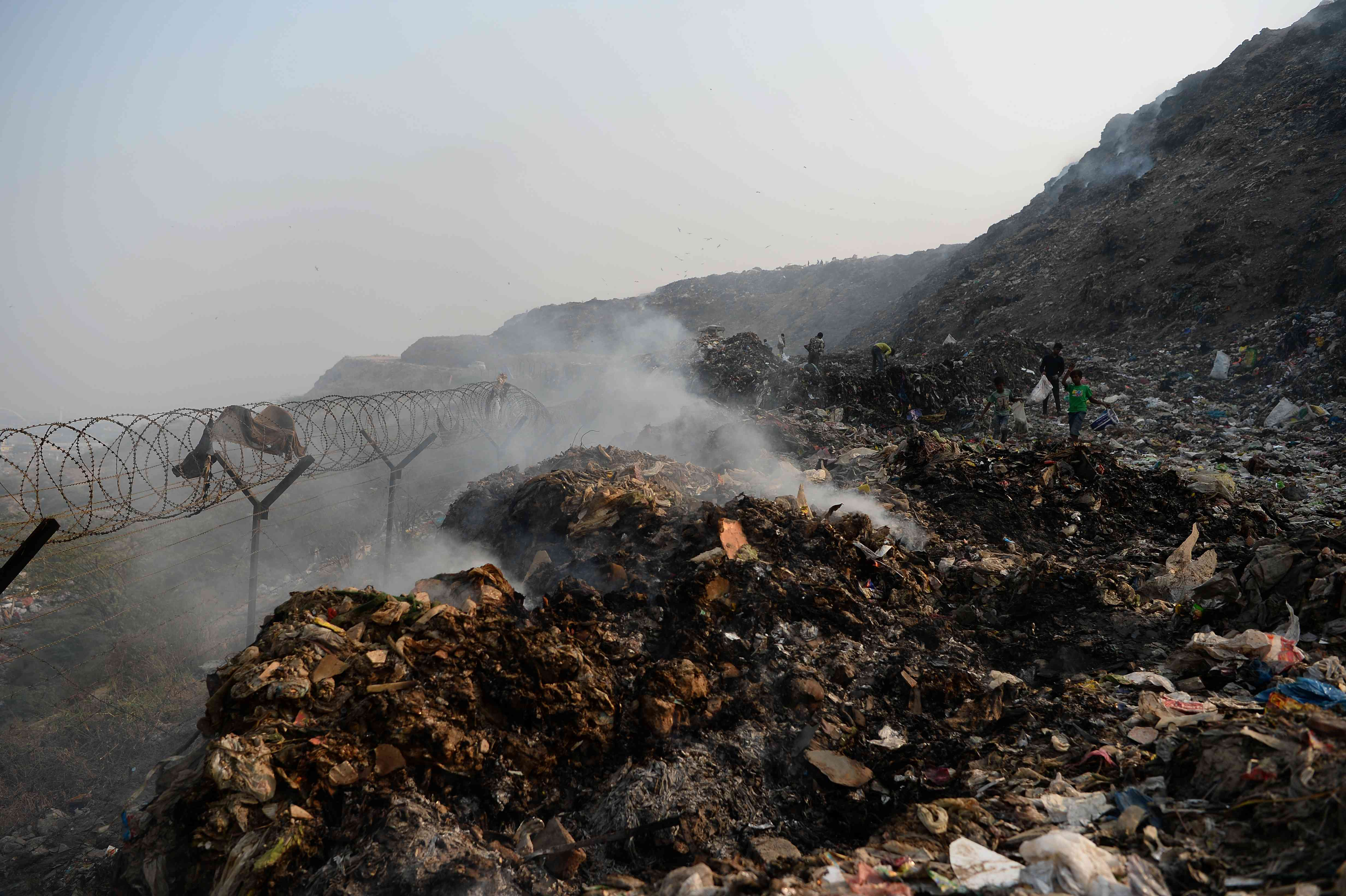 Smoke rises from the garbage at the Bhalswa landfill site. (Photo Credit: Sajjad Hussain/AFP).