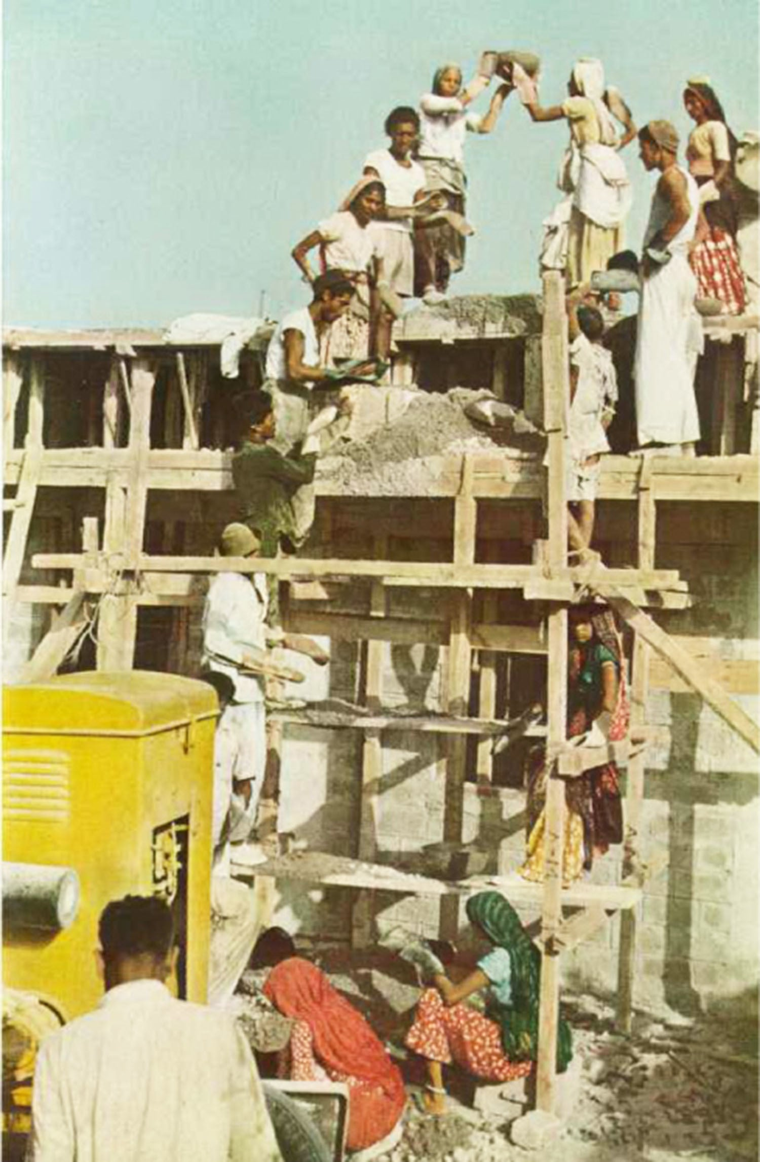 Men and women workers laying bricks during the construction of a building in 1952.