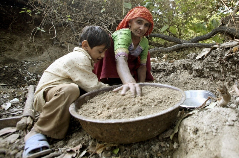 A Maldhari tribal woman and her child collect sand in the Gir forest in Gujarat. (Photo credit: Amit Dave/Reuters).