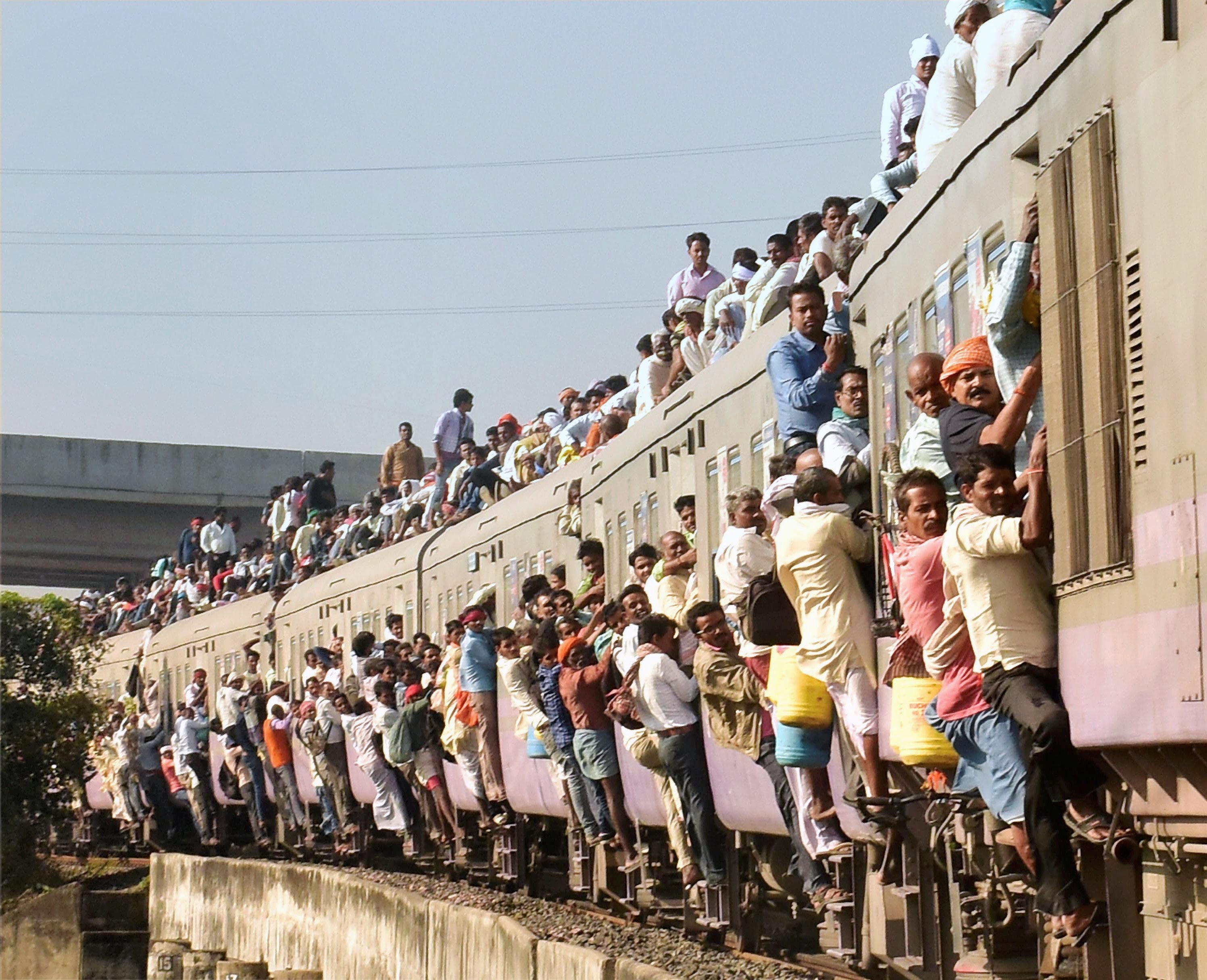 Passengers hang out of a train heading to Patna in Bihar, overcrowded by the Kartik Purnima rush . (Credit: PTI)