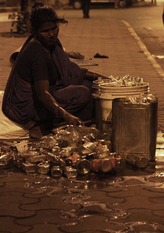 At midnight, some homeless families in King's Circle, Matunga give the final touches to already cleaned glass bottles, readying them for sale. Others in the same family make small temple hangings to be sold early in the morning.