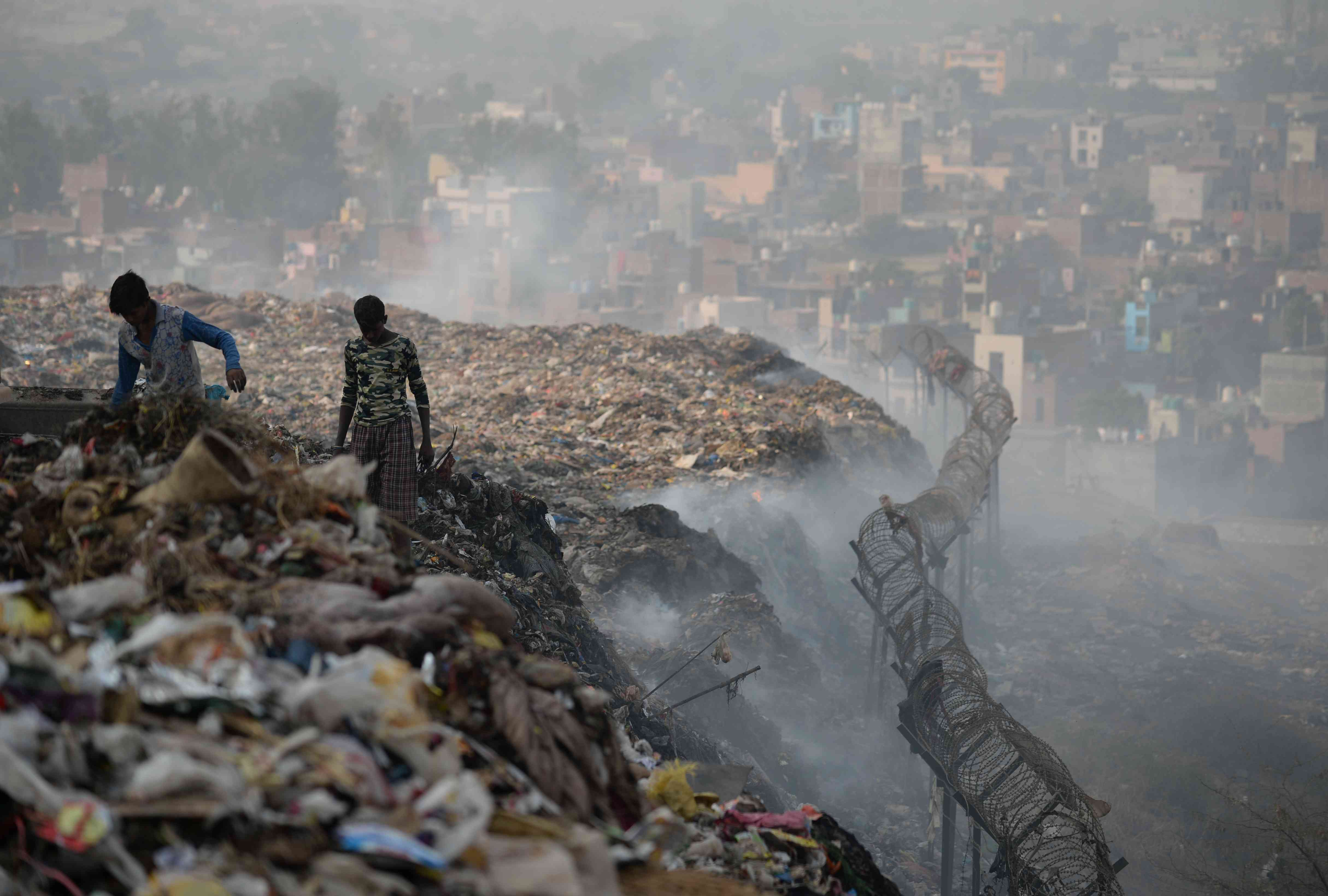Ragpickers sort through the mountain of garbage at Bhalswa for usable material. (Photo credit: Sajjad Hussain/AFP).