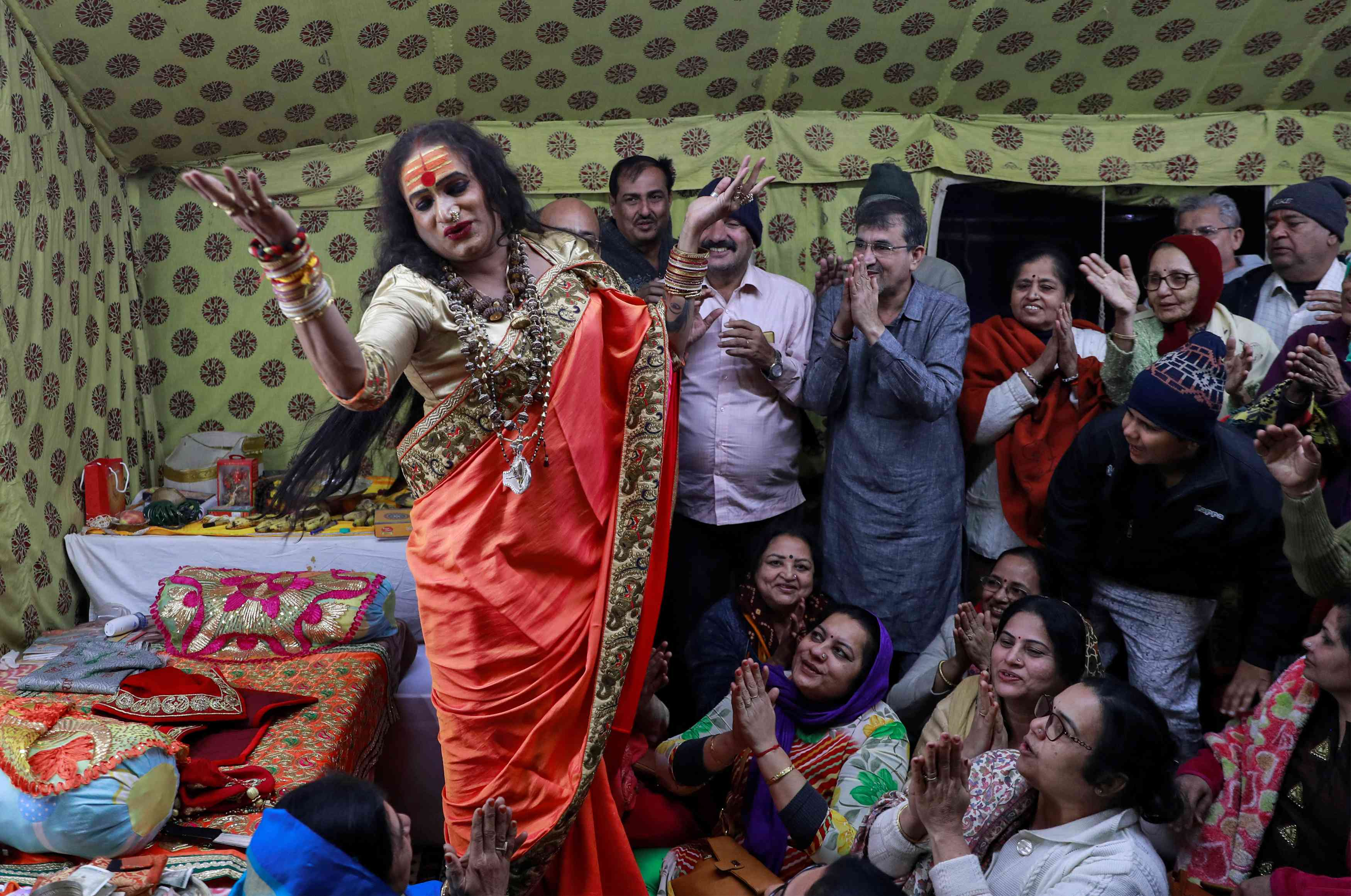 Lakshmi Narayan Tripathi, chief of the Kinnar Akhara, sings with her followers during on Monday. Credit: Danish Siddiqui/Reuters