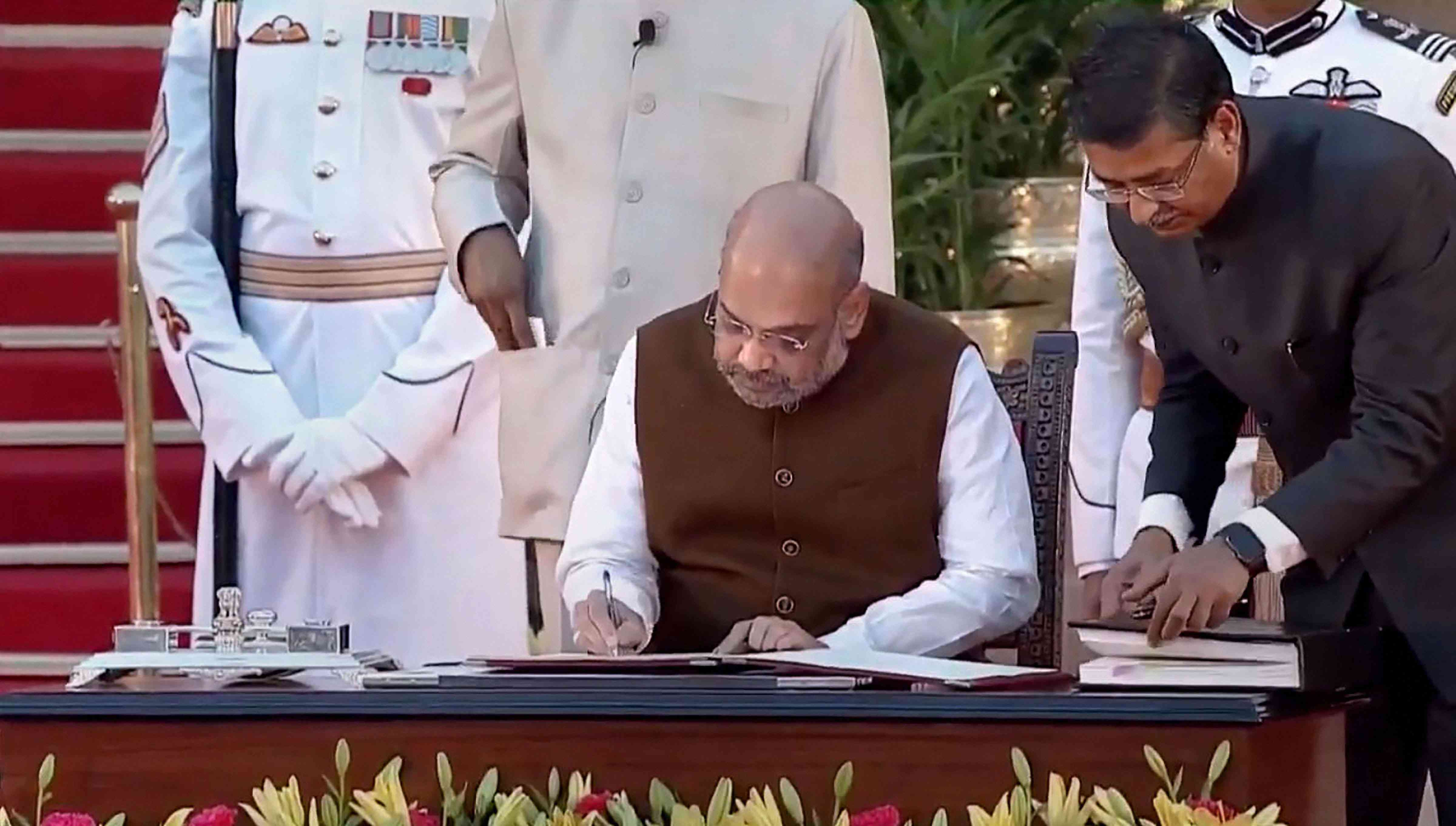 BJP President Amit Shah signs a register after taking oath as Union minister. (Image Credit: PTI)
