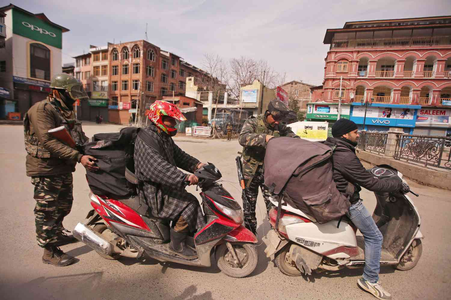 Central Reserve Police Force personnel check the bags of scooterists during restrictions after Kashmiri separatist called for shutdown to protest the arrest of their leaders in Srinagar on February 24, 2019. (Photo credit: Danish Ismail/Reuters).