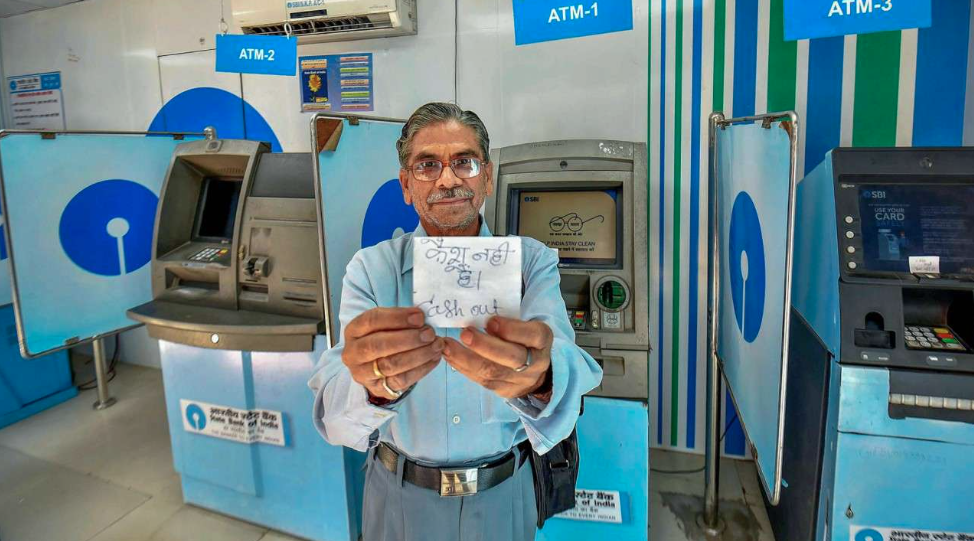 A man holds up an out-of-cash sign at an ATM in Patna in April. (Credit: PTI)