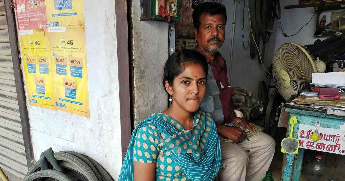 M Janani, 20, a college, with her father in their cycle repair shop in RN Palayam in Vellore in Tamil Nadu